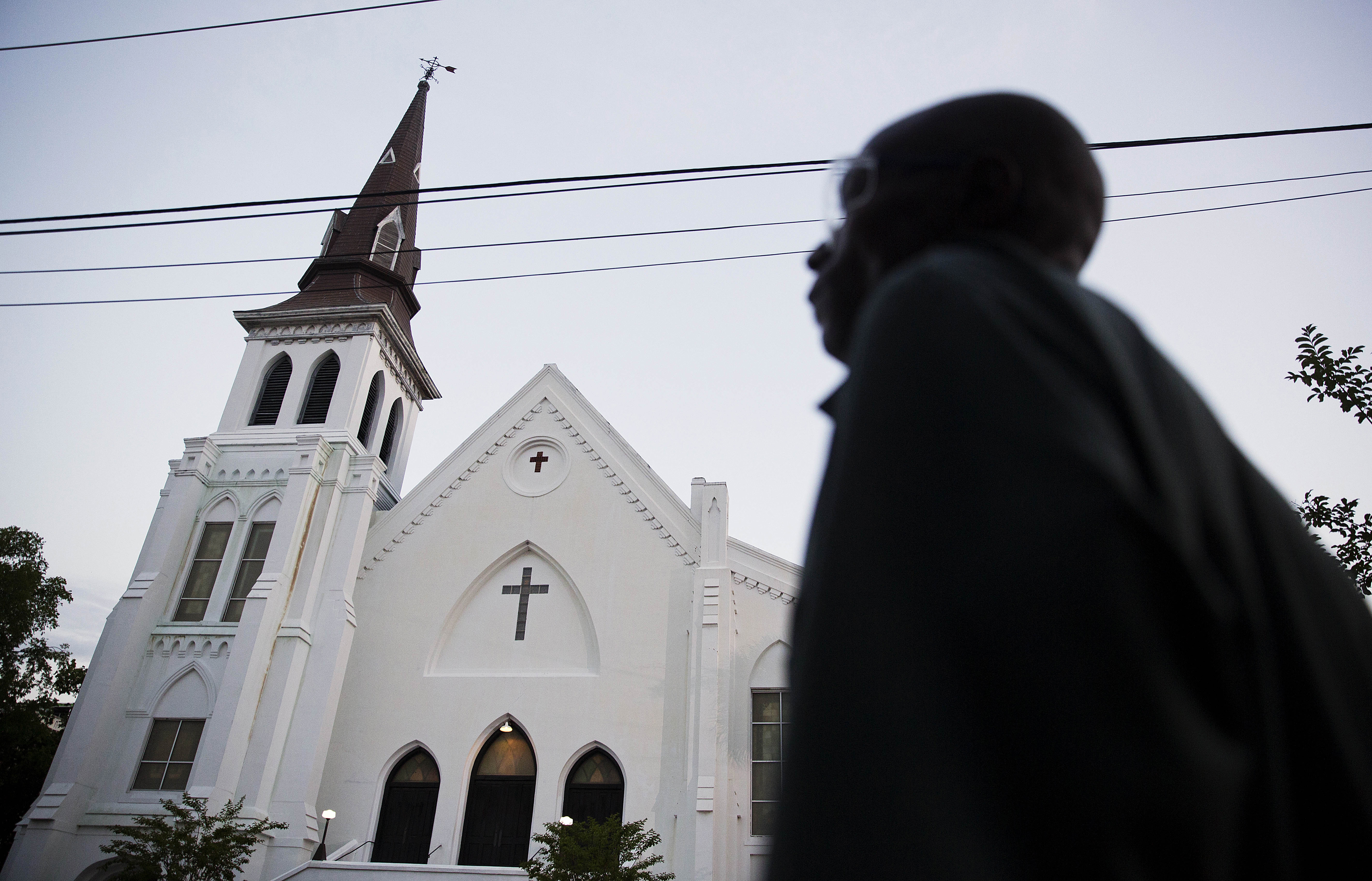 The steeple of Emanuel African Methodist Episcopal Church stands as a pedestrian passes early on June 21, 2015, in Charleston, S.C.
