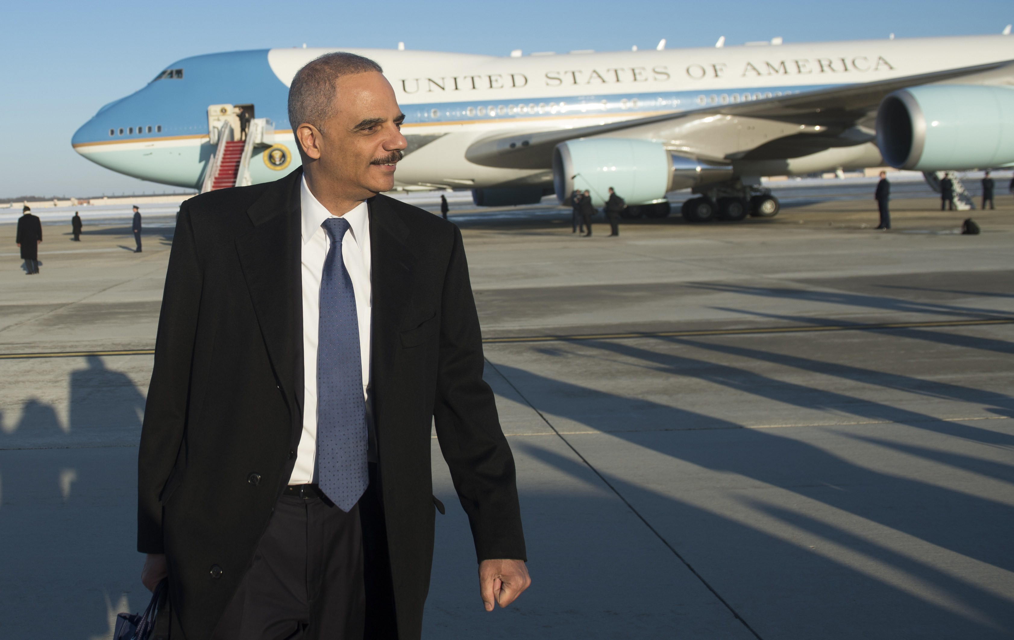 Attorney General Eric Holder walks from Air Force One after arriving with US President Barack Obama at Andrews Air Force Base in Maryland, March 6, 2015.