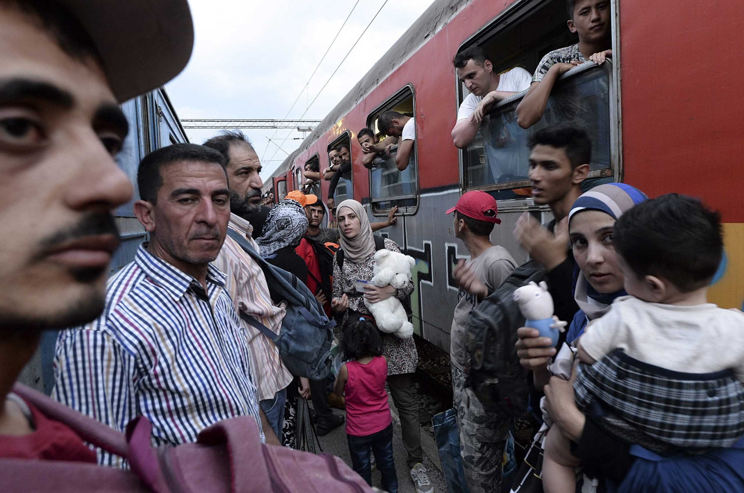 Migrants react after they couldn't find a seat on the train heading to the Serbian border, where they will migrate towards Western European nations, at the train station in Gevgelija, Macedonia, July 26, 2015.
