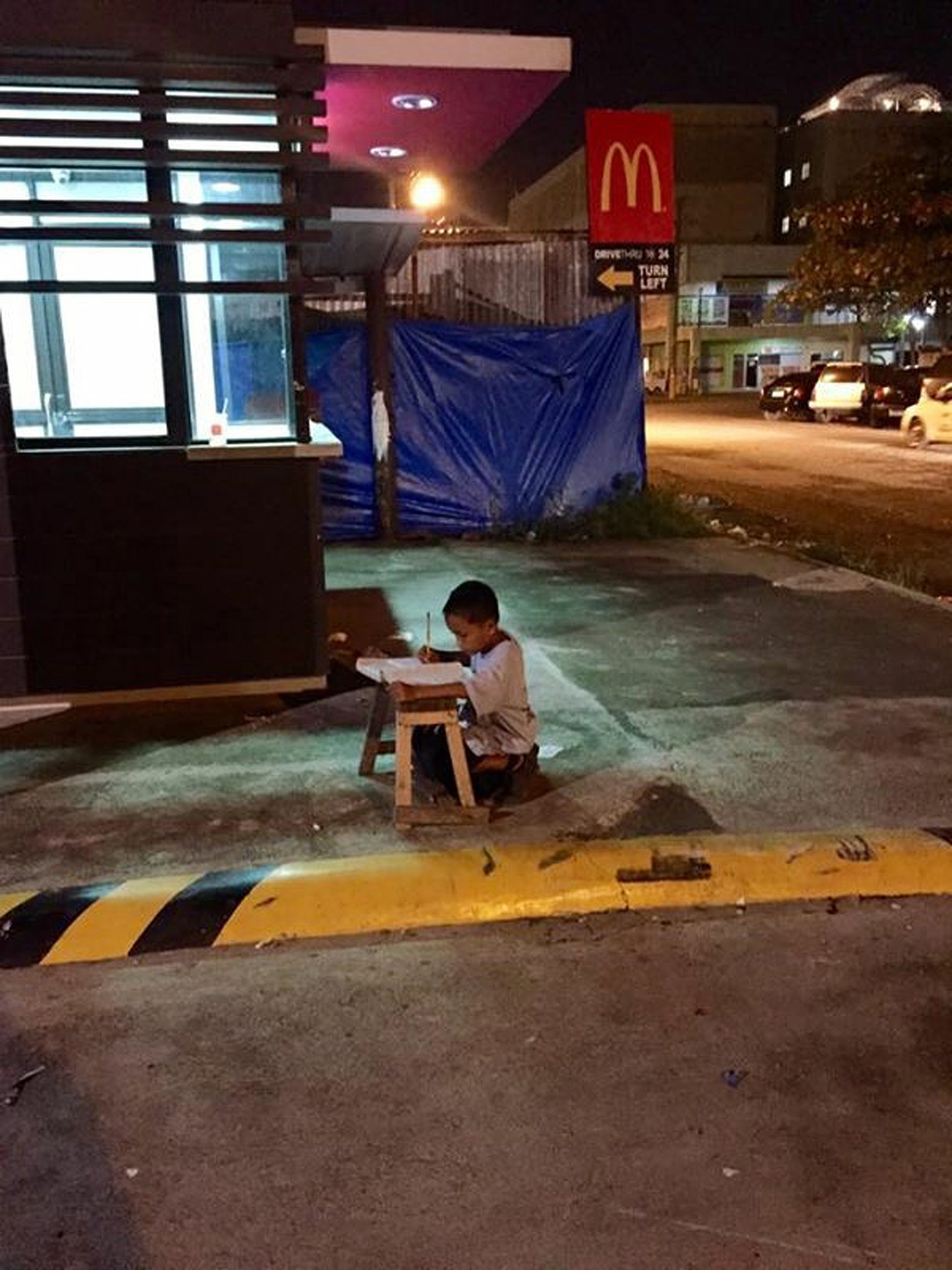 This handout photo taken on June 23, 2015 by student Joyce Torrefranca and released to AFP on July 10, 2015 shows homeless nine-year-old boy Daniel Cabrera doing his homework on a wooden stool placed close to a fastfood restaurant to catch the light from the store in Mandaue in the central Philippines.