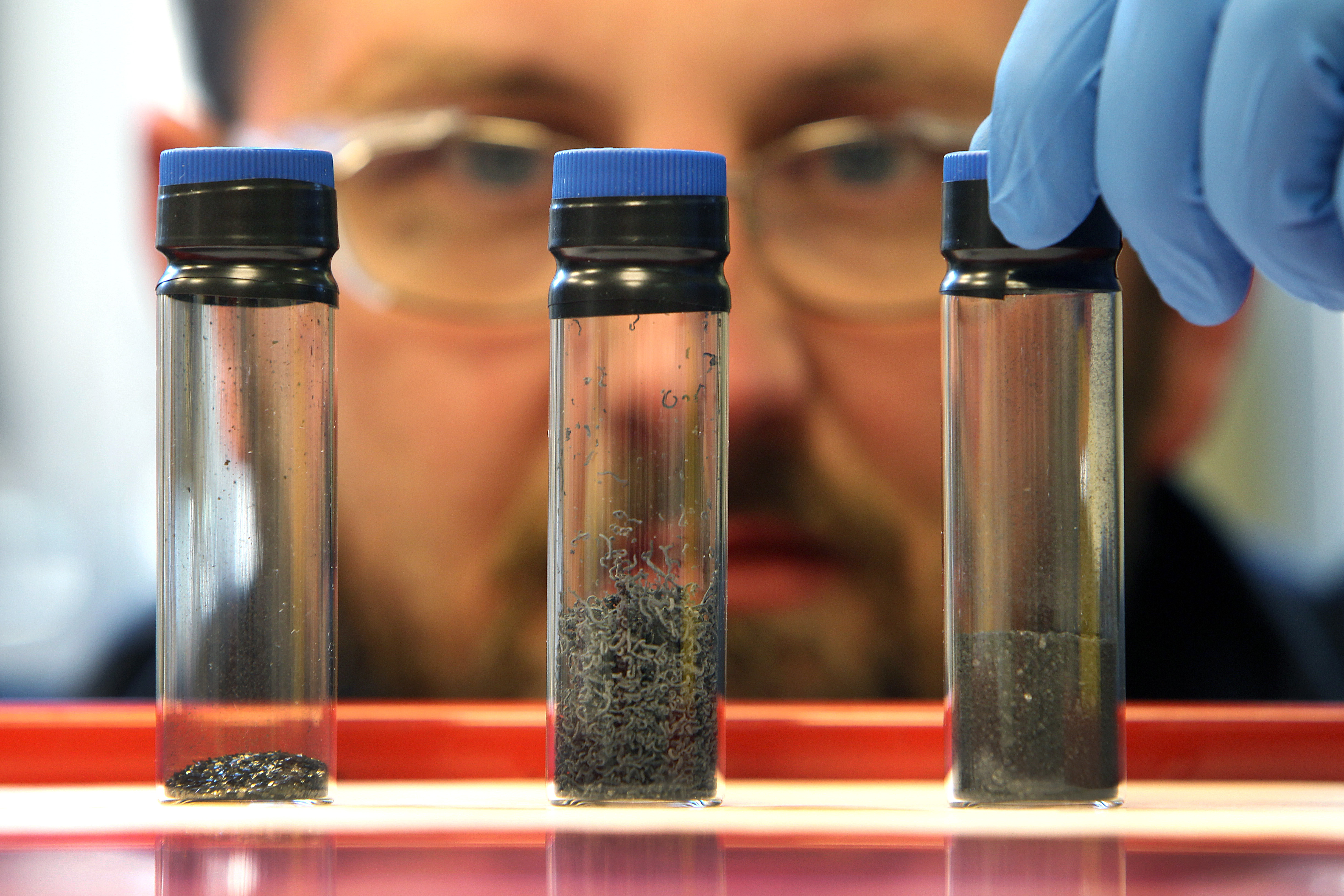 BILLERICA, MA - JANUARY 4: At Cabot Corporation, Senior Researcher Matt Hesketh examines the progression of graphene in three vials. The vial on the left is graphite, the middle one is graphite expanded, and the one on the right is graphene. (Photo by John Tlumacki/The Boston Globe via Getty Images)