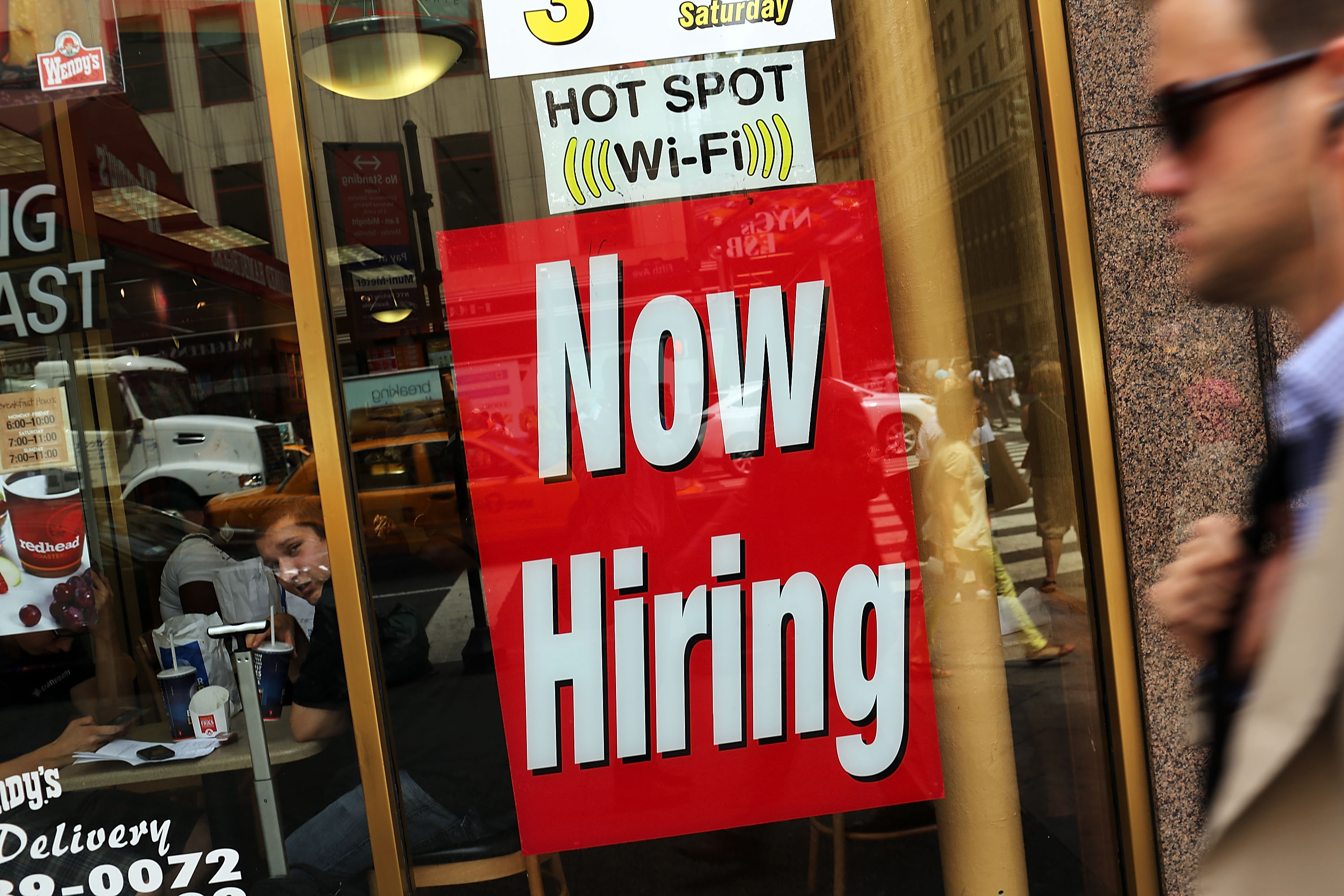 A  now hiring  sign is viewed in the window of a fast food restaurant on August 7, 2012 in New York City.