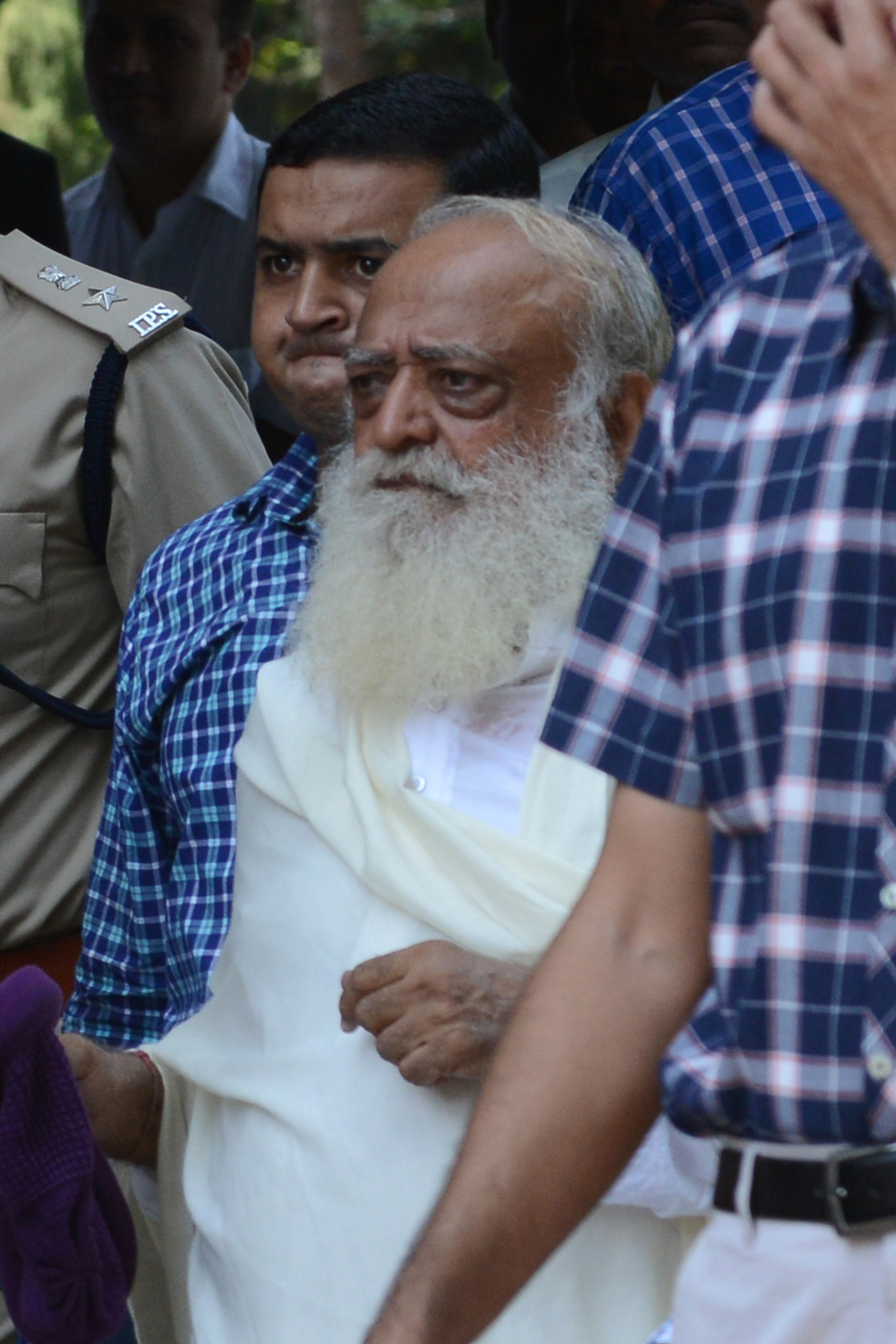 Indian spiritual guru Asaram Bapu is escorted by state police as he arrives at a local court in Gandhinagar, some 30 kms. from Ahmedabad, on October 15, 2013.