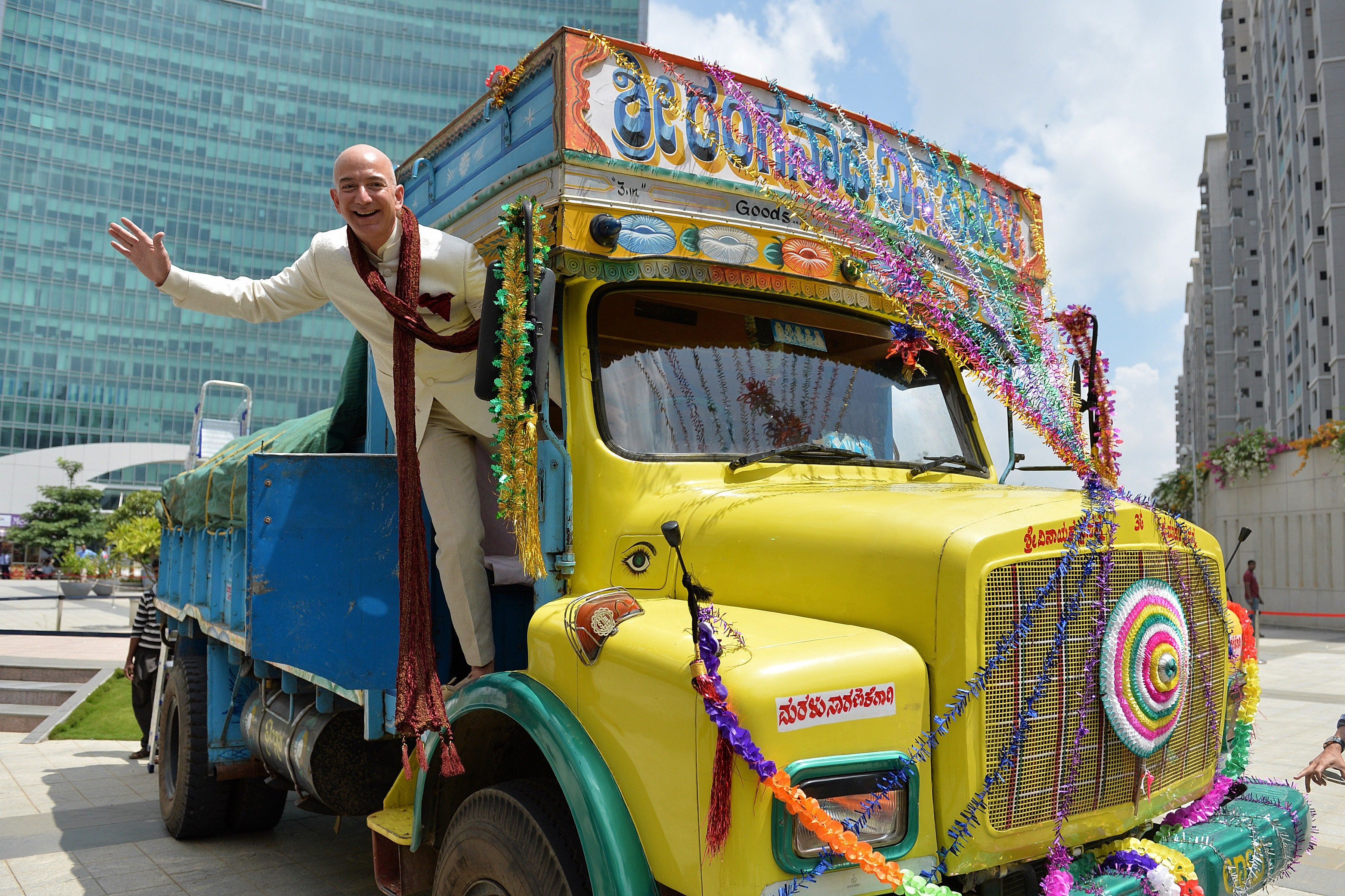CEO of Amazon.com Jeff Bezos poses on a lorry in Bangalore on Sept. 28, 2014