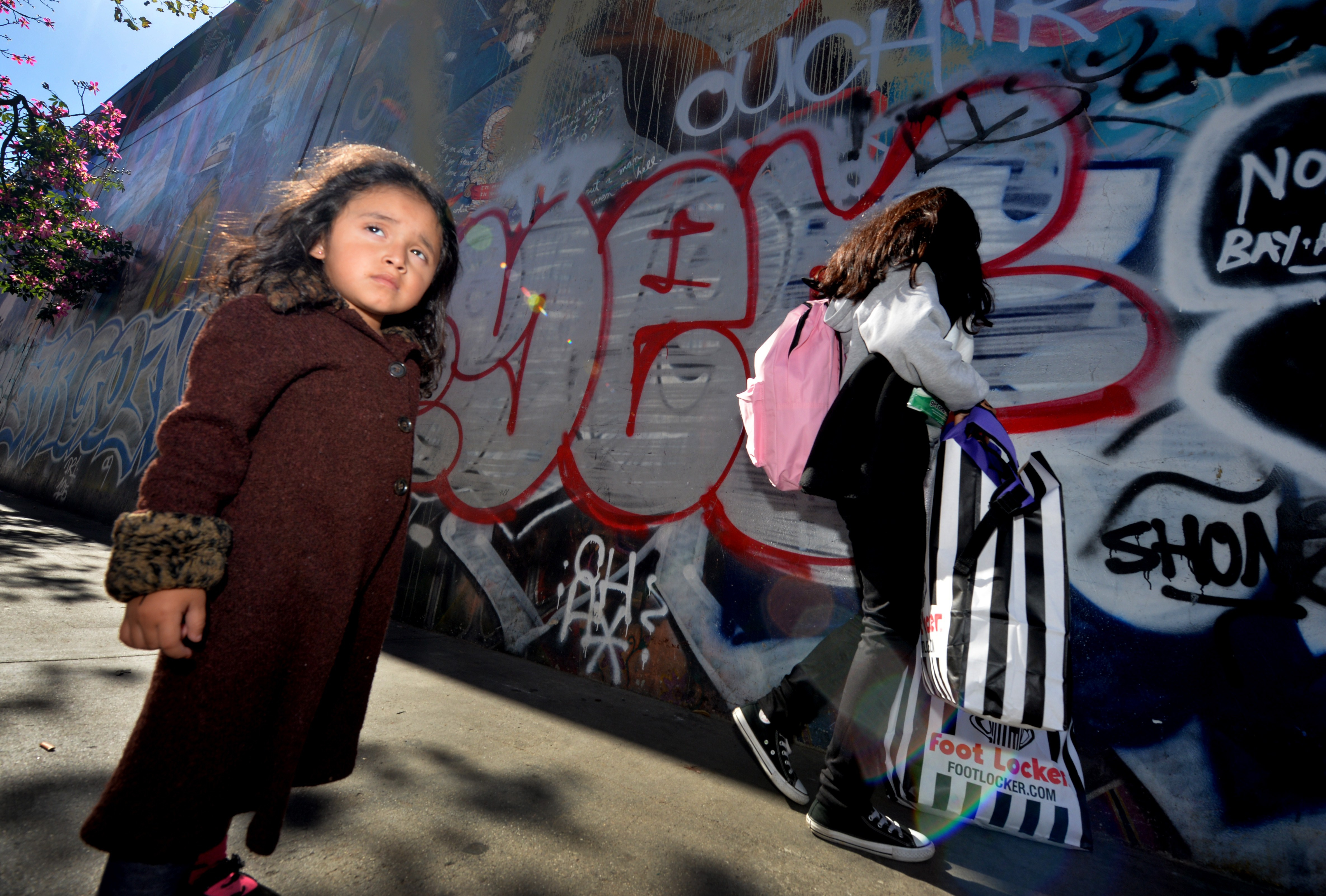 Three year old Saria Amaya (L) waits with her mother after receiving shoes and school supplies during a charity event to help more than 4,000 underprivileged children at the Fred Jordan Mission in the Skid Row area of Los Angeles on October 2, 2014.
