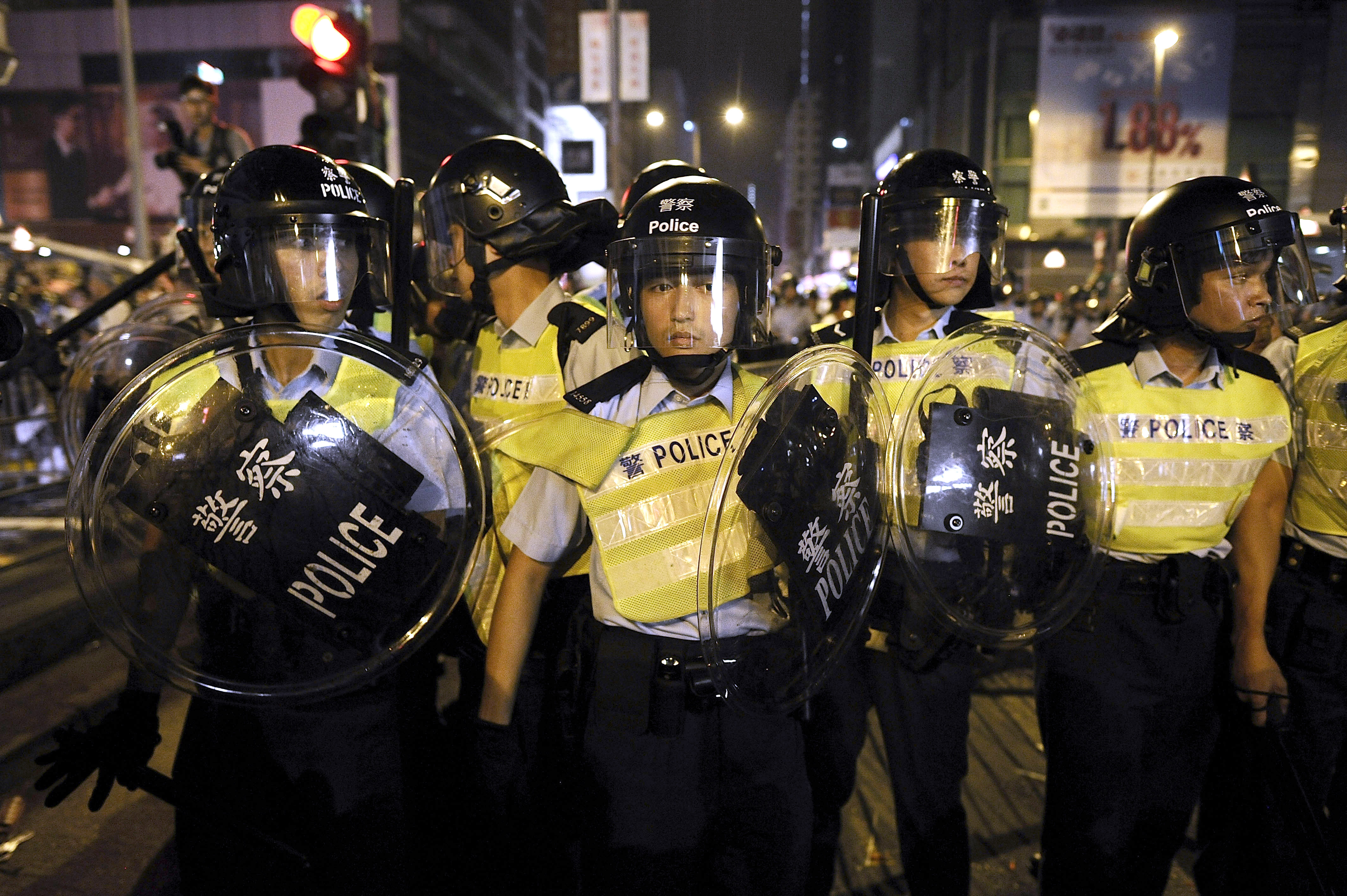 Riot police forces clash with pro-democracy protesters shortly after midnight at Mong Kok on October 19, 2014 in Hong Kong.