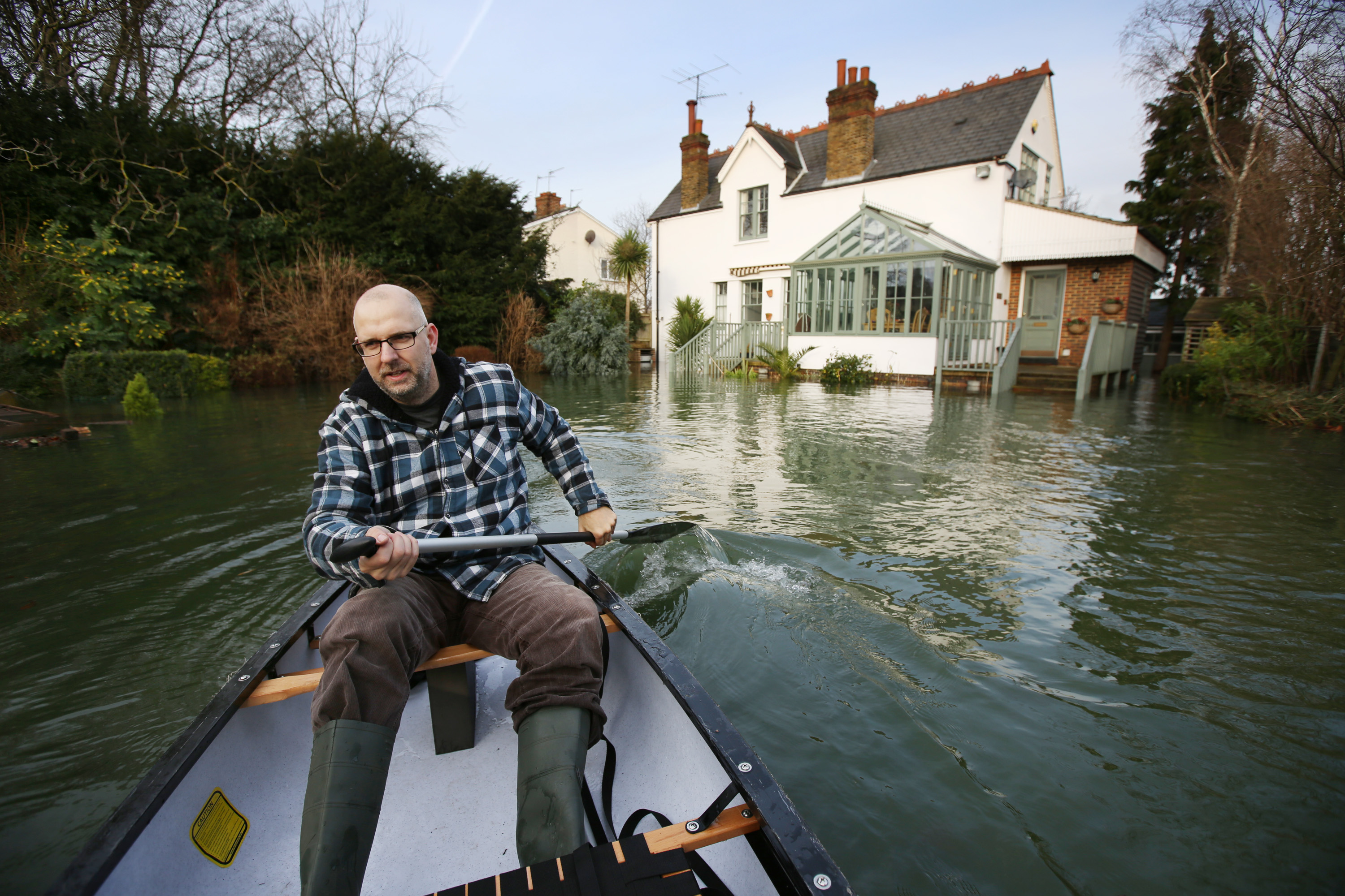 Ian Berry paddles a canoe through his front garden after the River Thames flooded on January 8, 2014 in Chersey, England.