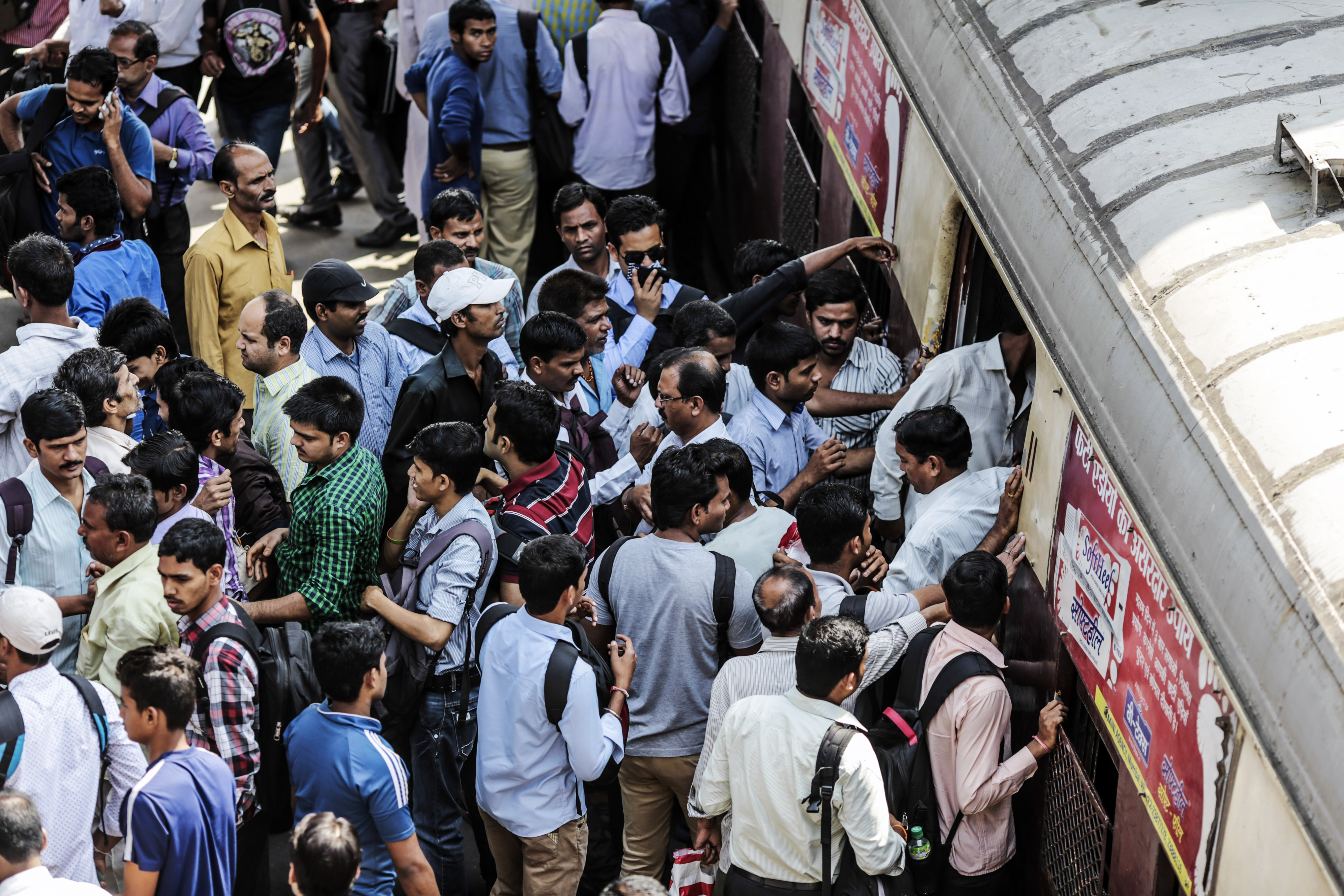 Passengers disembark as commuters wait to board a train during the morning rush hour at Kurla railway station in Mumbai, India, on Wednesday, April 15, 2015.