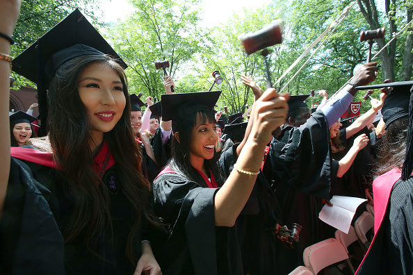 CAMBRIDGE, MA - MAY 28: Law school graduates wielded their gavels, including Tiffany Quach, left, and Angela K. Antony. Harvard University holds its commencement exercises at the Tercentenary Theatre, on Thursday, May 28, 2015. (Photo by Pat Greenhouse/The Boston Globe via Getty Images)