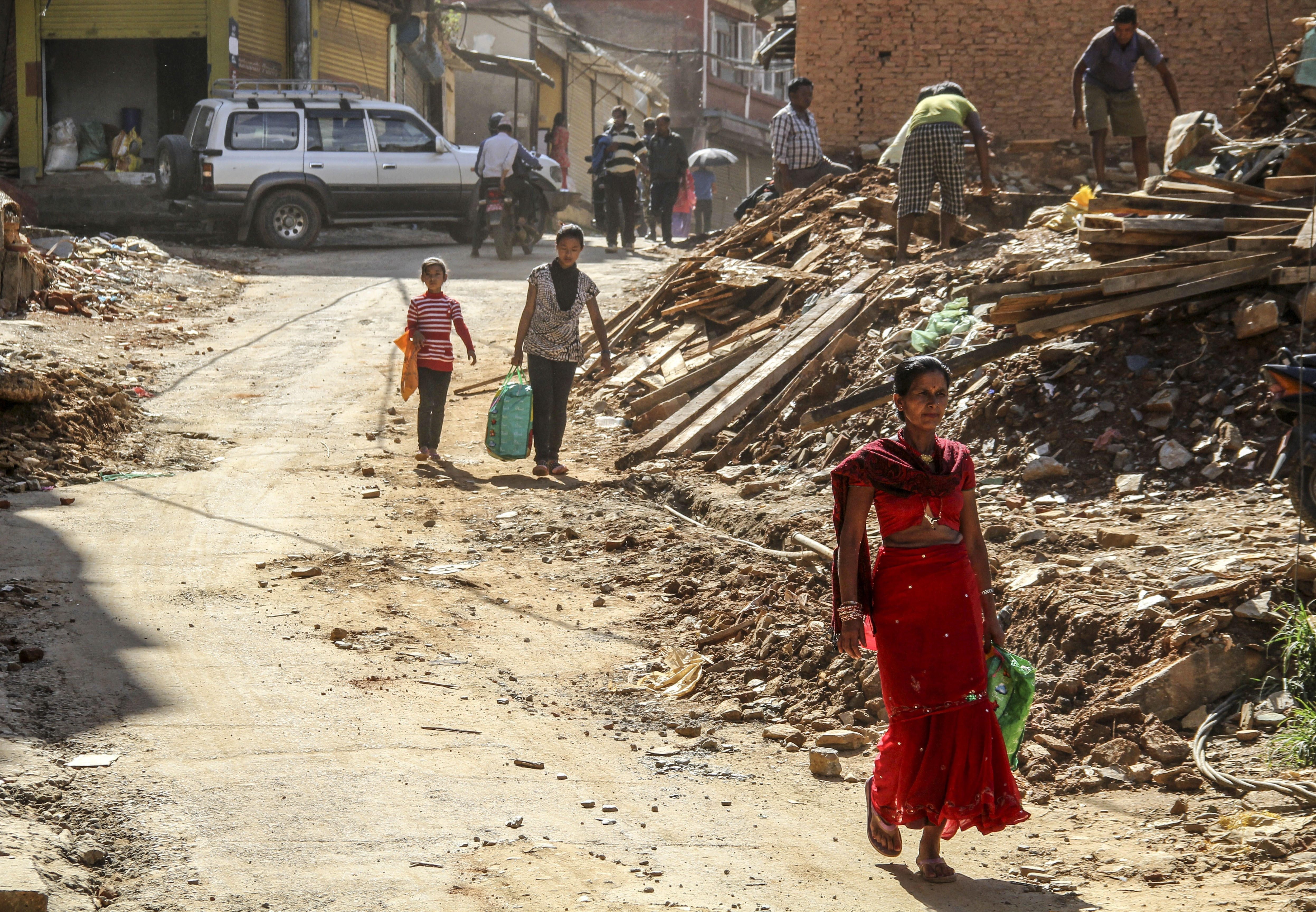 Nepali people walk amid the debris of destroyed houses in Sindhupalchowk, Nepal, on June 17, 2015