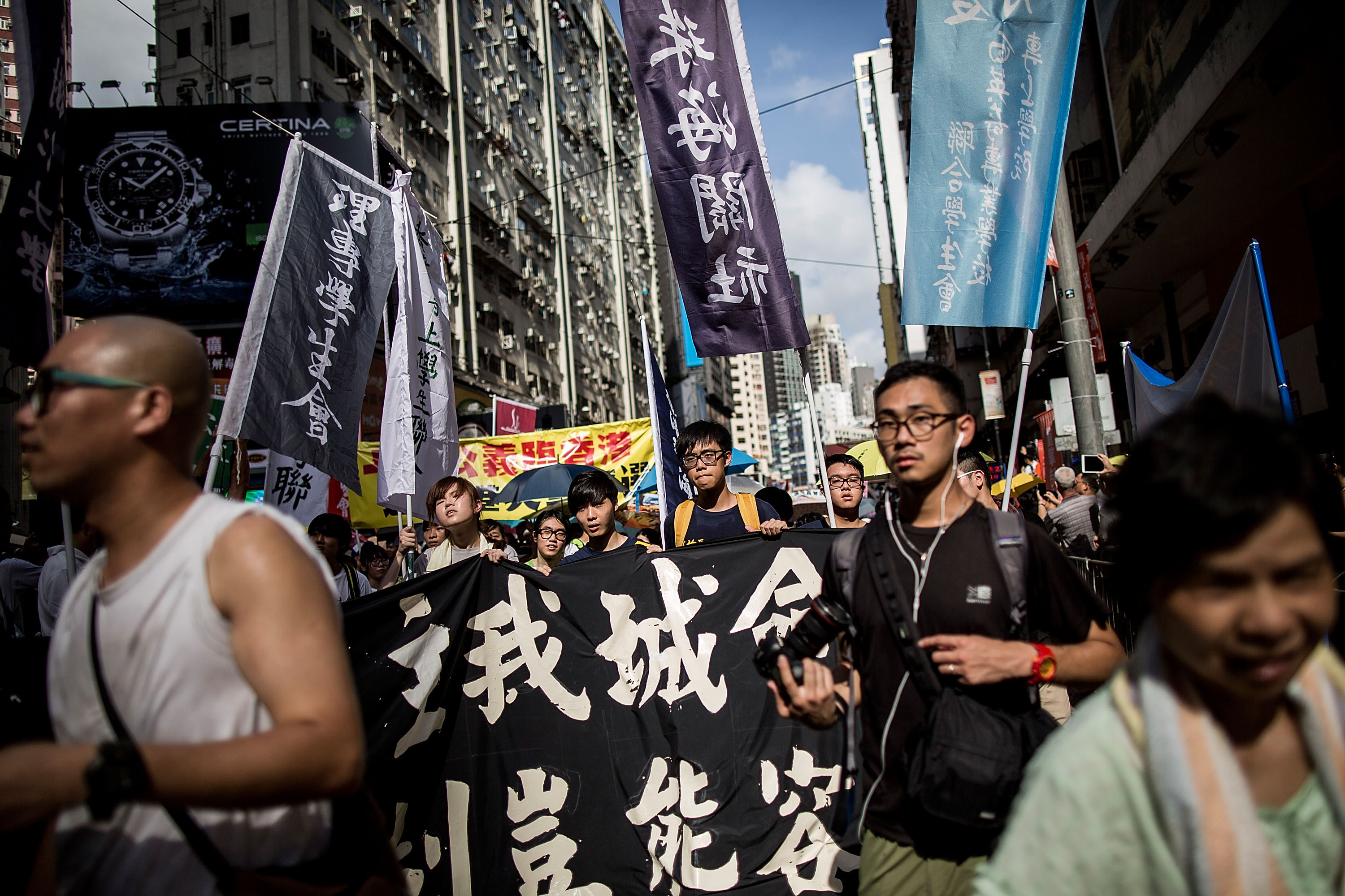 Protesters march on a street during a rally as they hold banners and shout slogans on July 1, 2015 in Hong Kong.