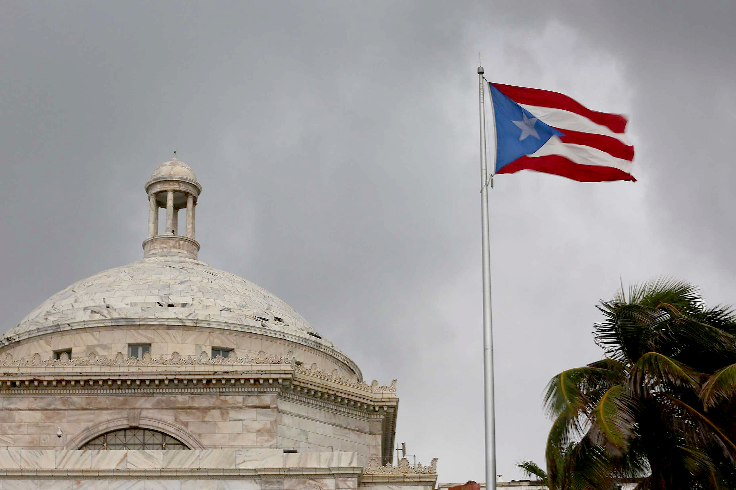 The Puerto Rican flag flies near the Capitol building as the island's residents deal with the government's $72 billion debt on July 1, 2015 in San Juan.