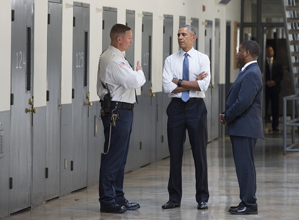 President Barack Obama, alongside Charles Samuels (R), Bureau of Prisons Director, and Ronald Warlick (L), a correctional officer, tours a cell block at the El Reno Federal Correctional Institution in El Reno, Oklahoma, on July 16, 2015.