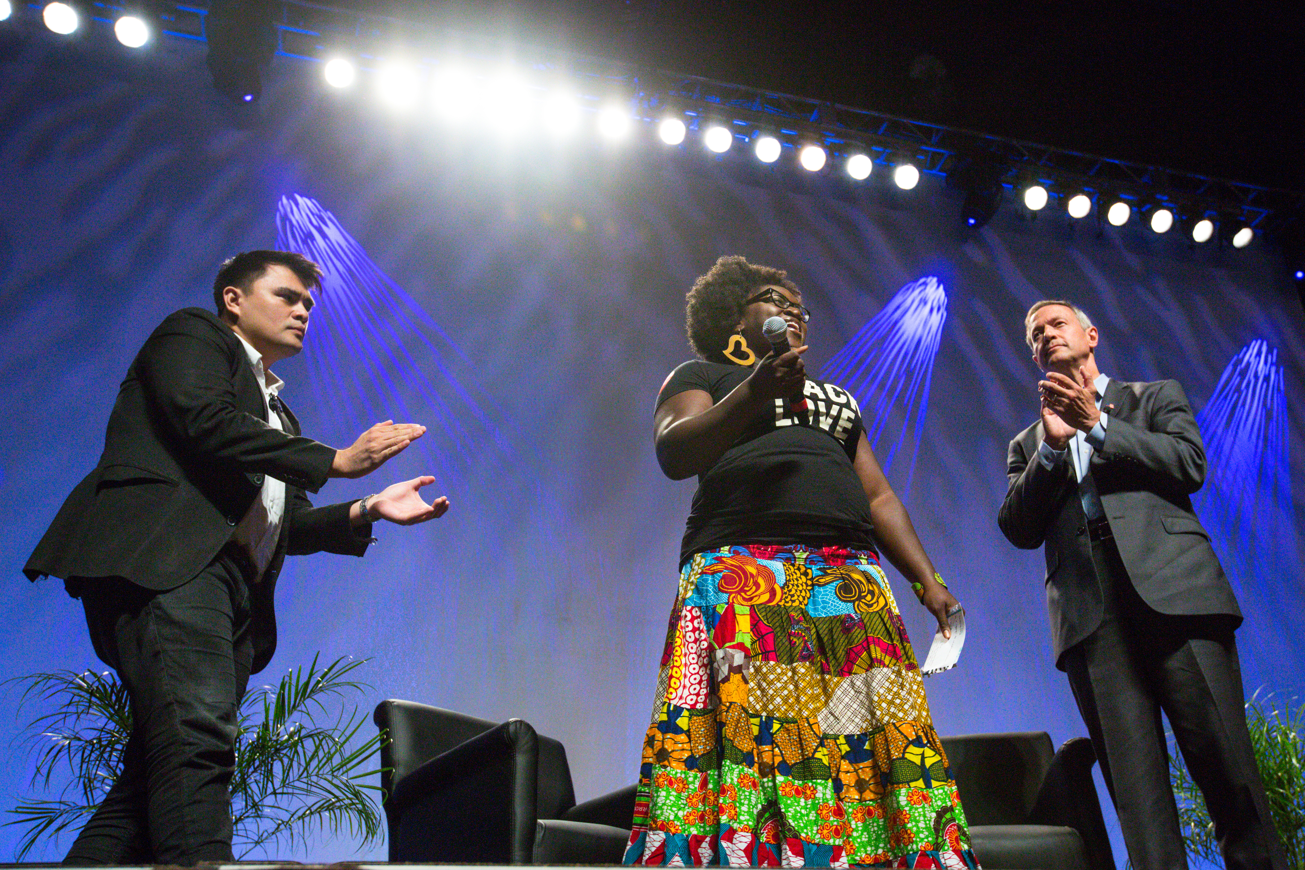 Former Gov. Martin O'Malley (D-MD) (R), and moderator Jose Antonio Vargas (R), listen to Tia Oso, the National Coordinator for the Black Immigration Network, during an interruption to O'Malley's speech, at the Netroots Nation 2015 Presidential Town Hall with at the Phoenix Convention Center on July 18, 2015 in Phoenix.
