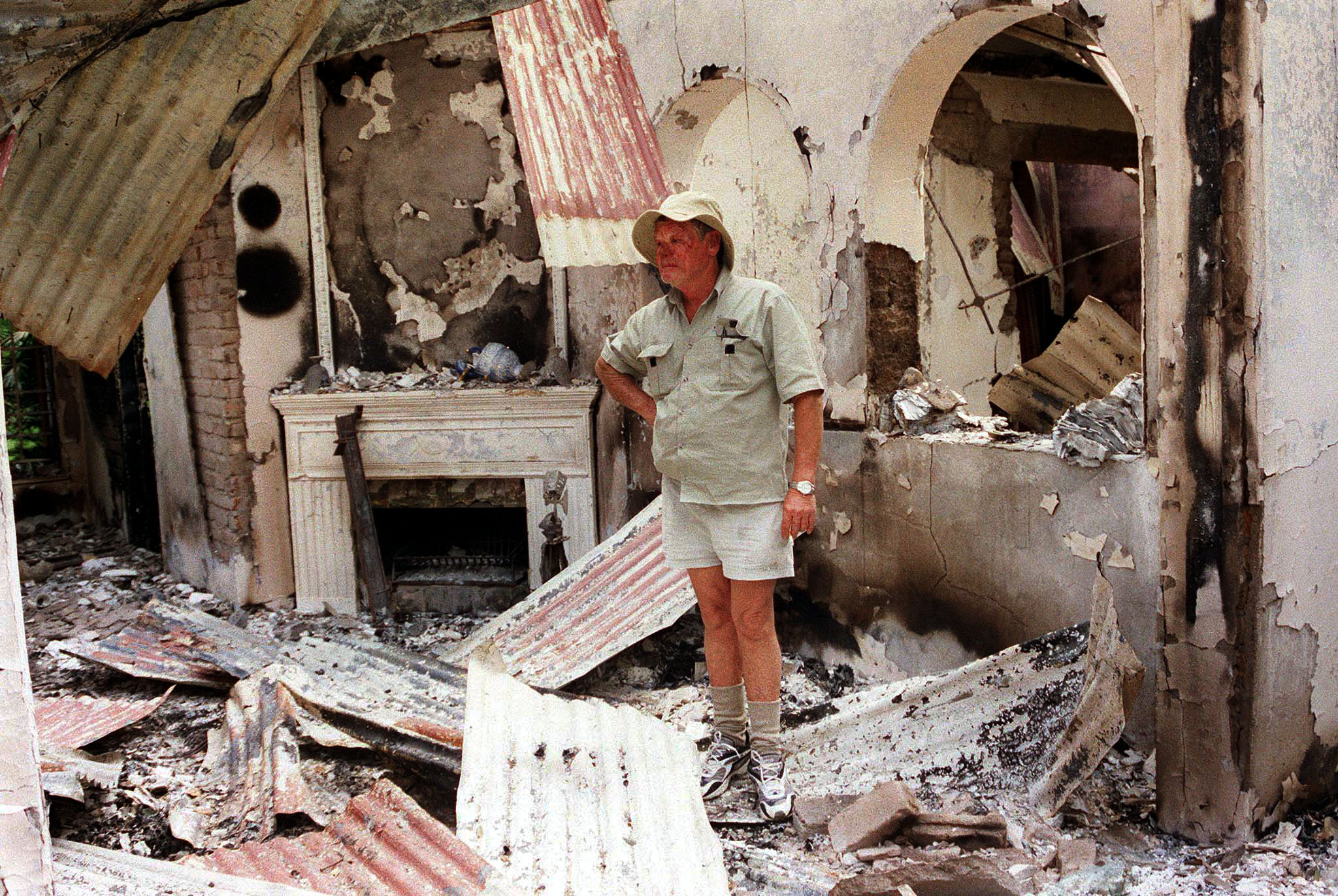In this file photo from 2002, Dup Muller, 59, a commercial farmer in Headlands, 110 kilometers, (70 miles) East of Harare, stands in the burned out ruins of his farm house, which  was attacked by war veterans enforcing a government order for whites to leave their farms.