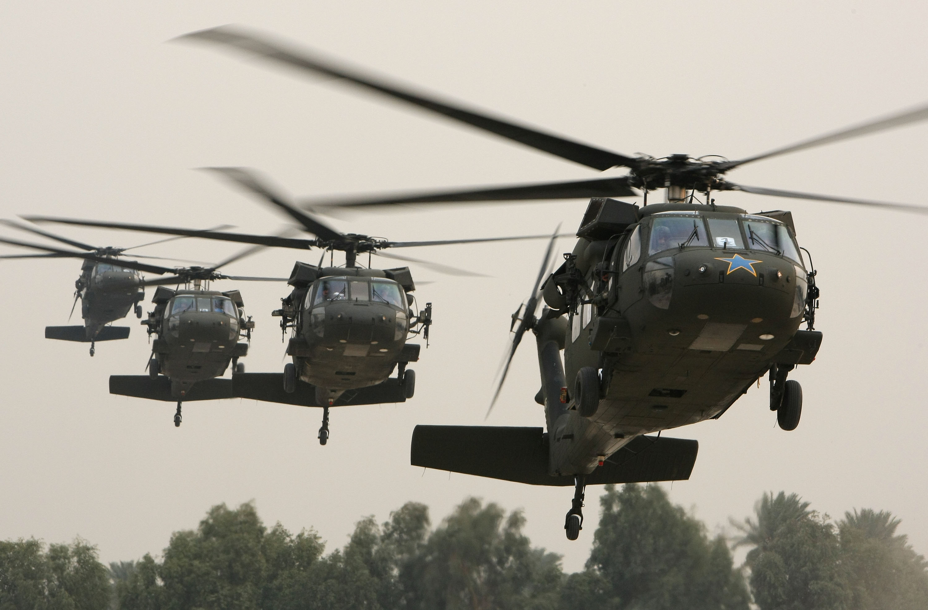 A Blackhawk helicopter (R) carrying U.S. Secretary of Defense Robert Gates arrives in the Green Zone December 10, 2009 in Baghdad, Iraq.
