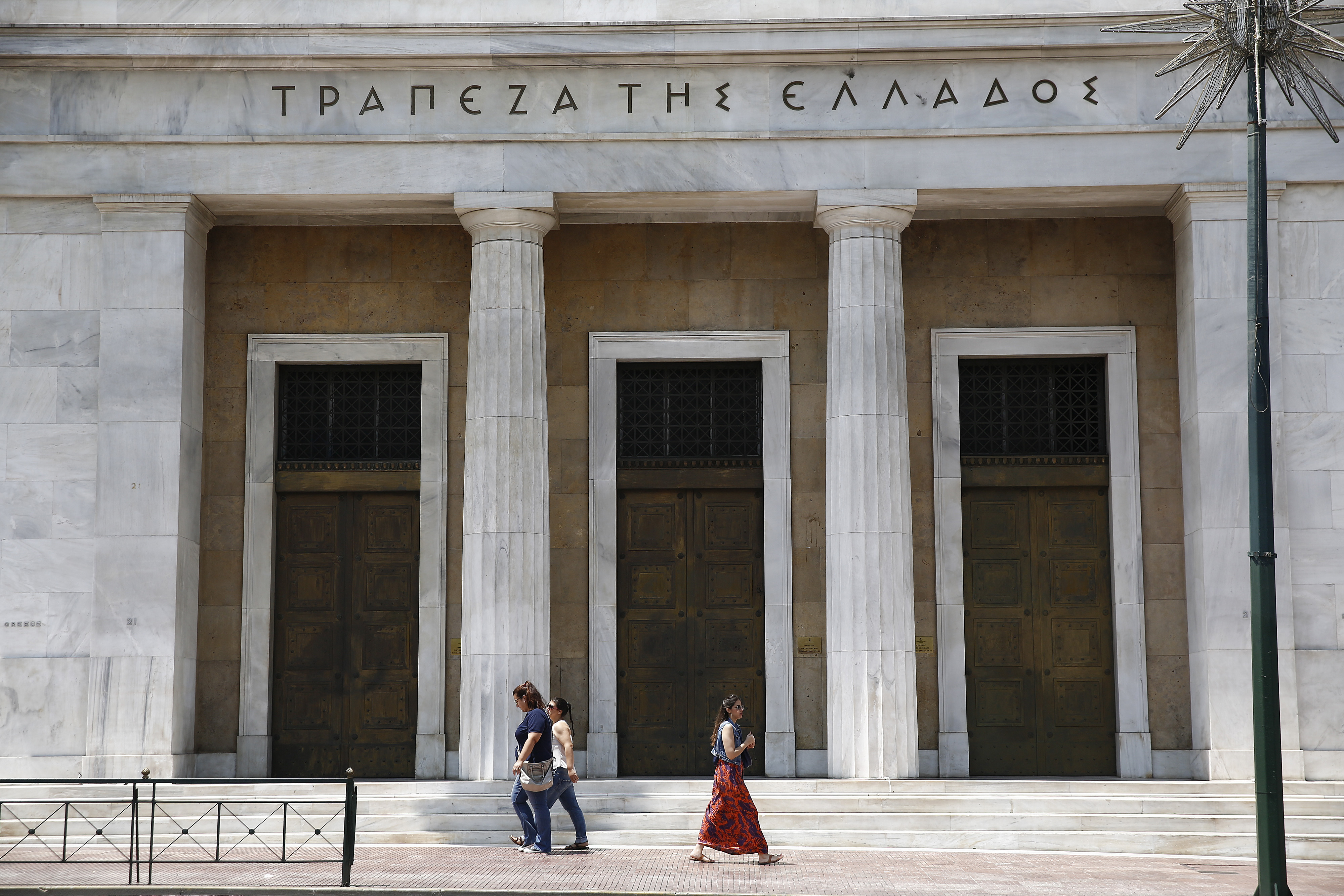 Pedestrians pass the headquarters of the Bank of Greece SA, Greece's central bank, in Athens on June 28, 2015.