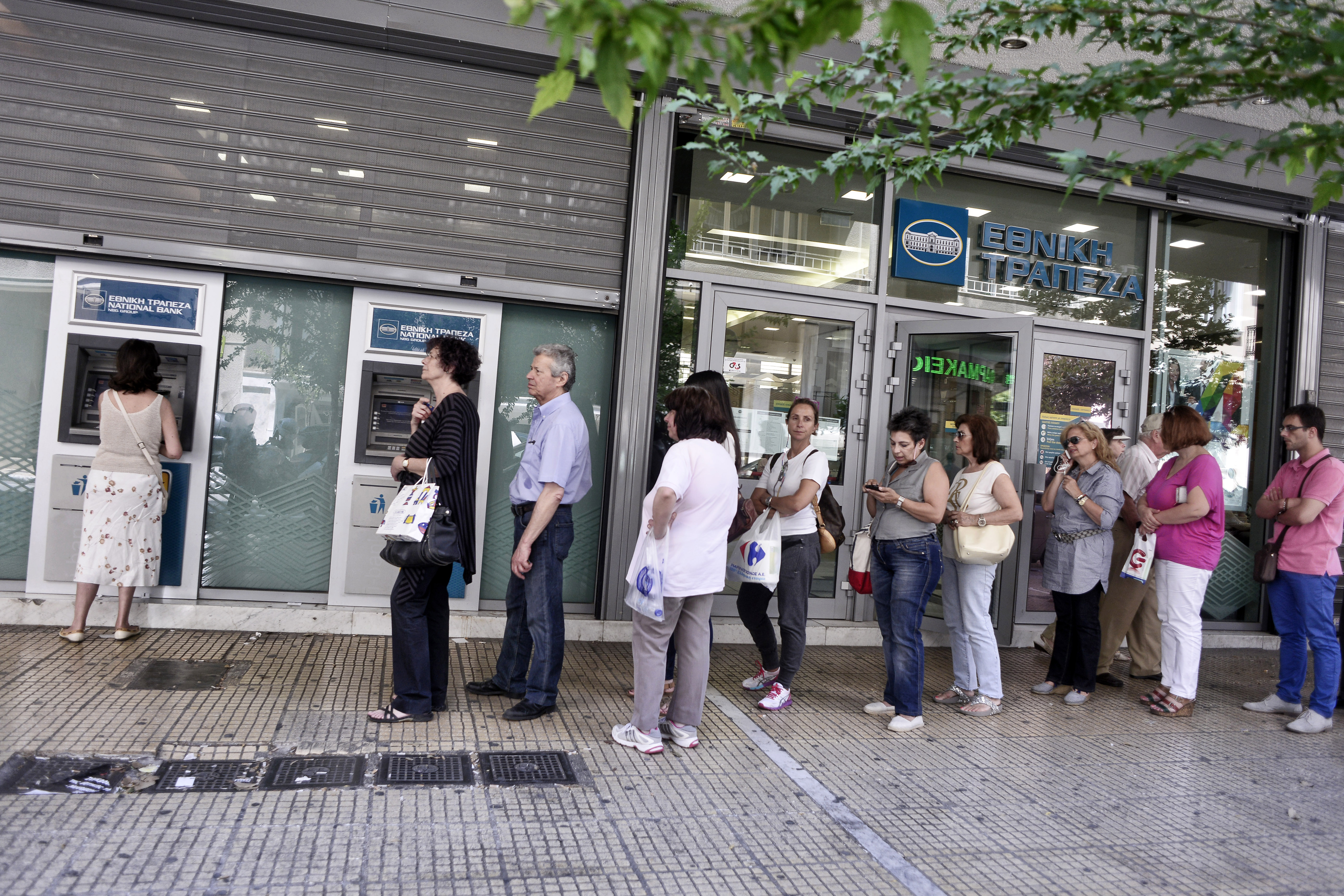 People line up at an ATM machine outside a bank on July 6, 2015 in Athens.