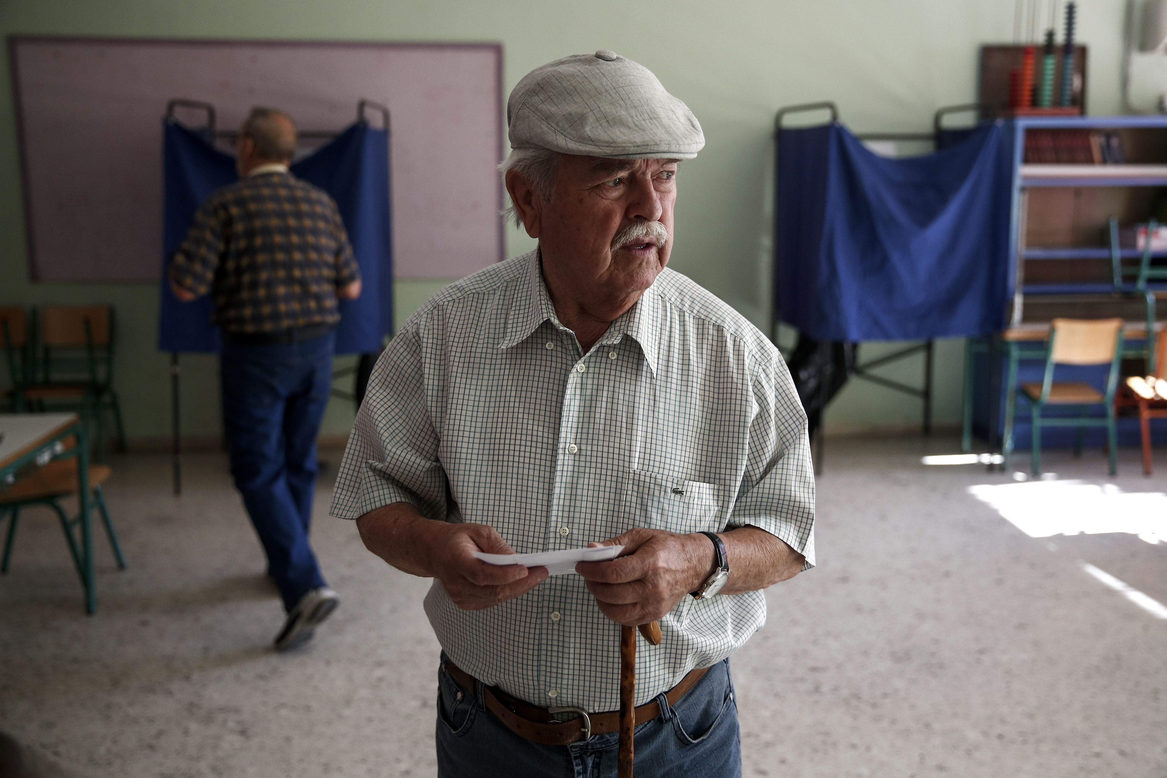 A voter holds a ballot and an envelope before voting for the Greek referendum inside a polling station in Athens on July 5, 2015.