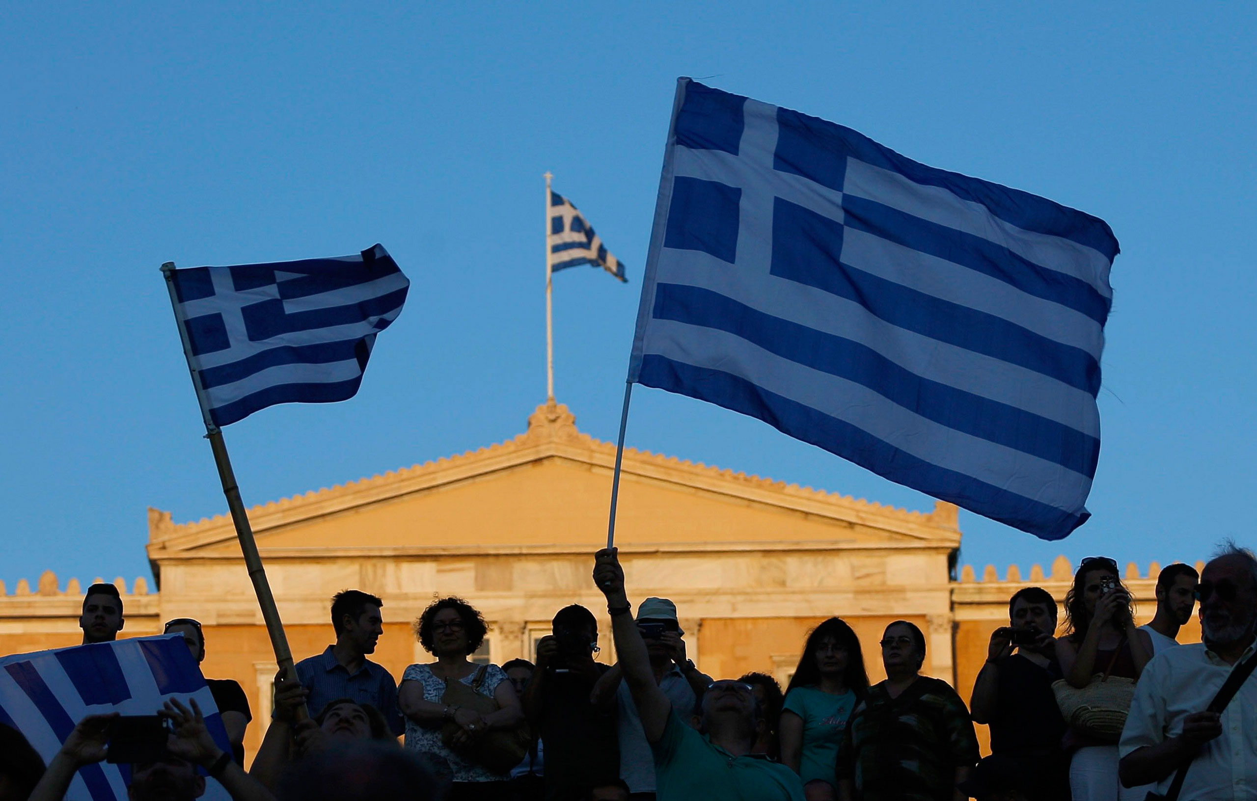 "Supporters of the ""No"" vote wave Greek flags after the referendum's exit polls at Syntagma square in Athens on July 5, 2015."