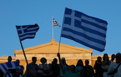 """Supporters of the """"No"""" vote wave Greek flags after the referendum's exit polls at Syntagma square in Athens, Sunday, July 5, 2015."""