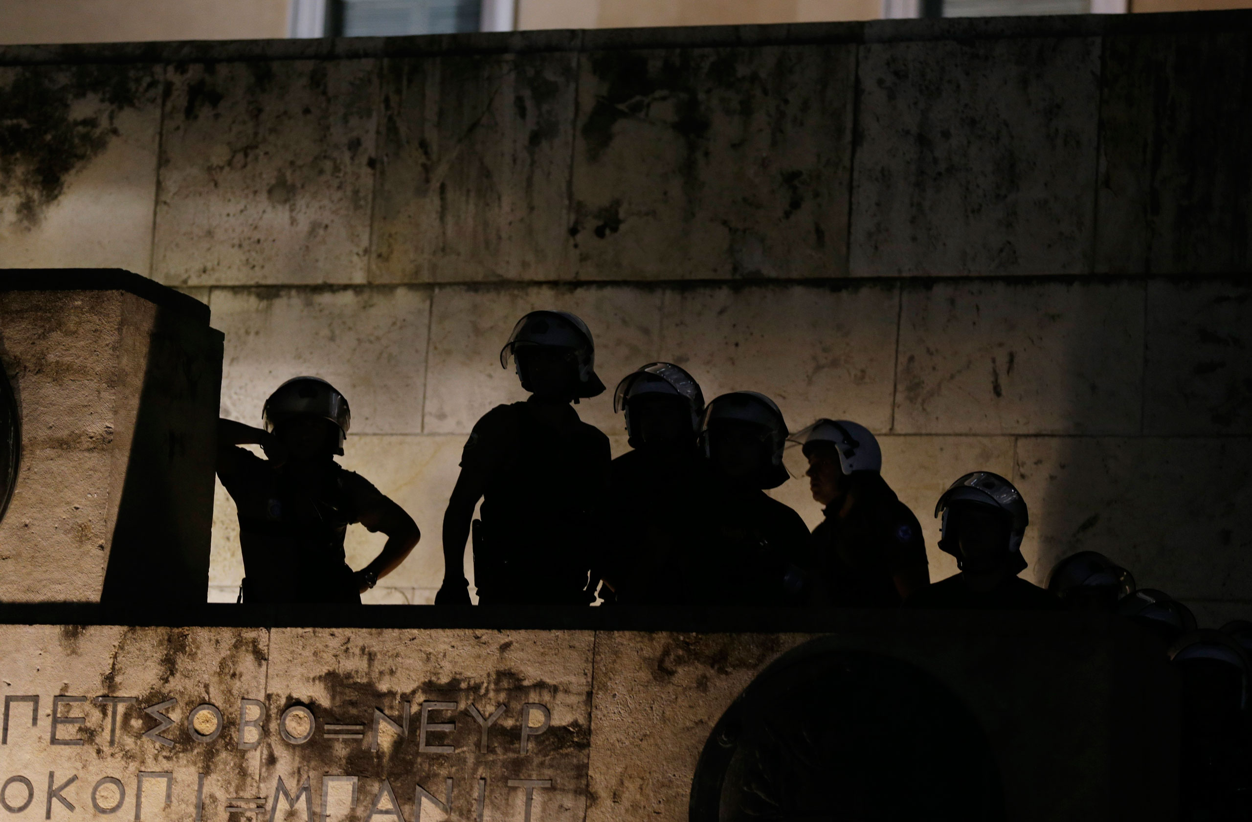 Riot policemen guard an entrance of the parliament as supporters of the No vote celebrate after the results of the referendum in Athens on July 5, 2015.