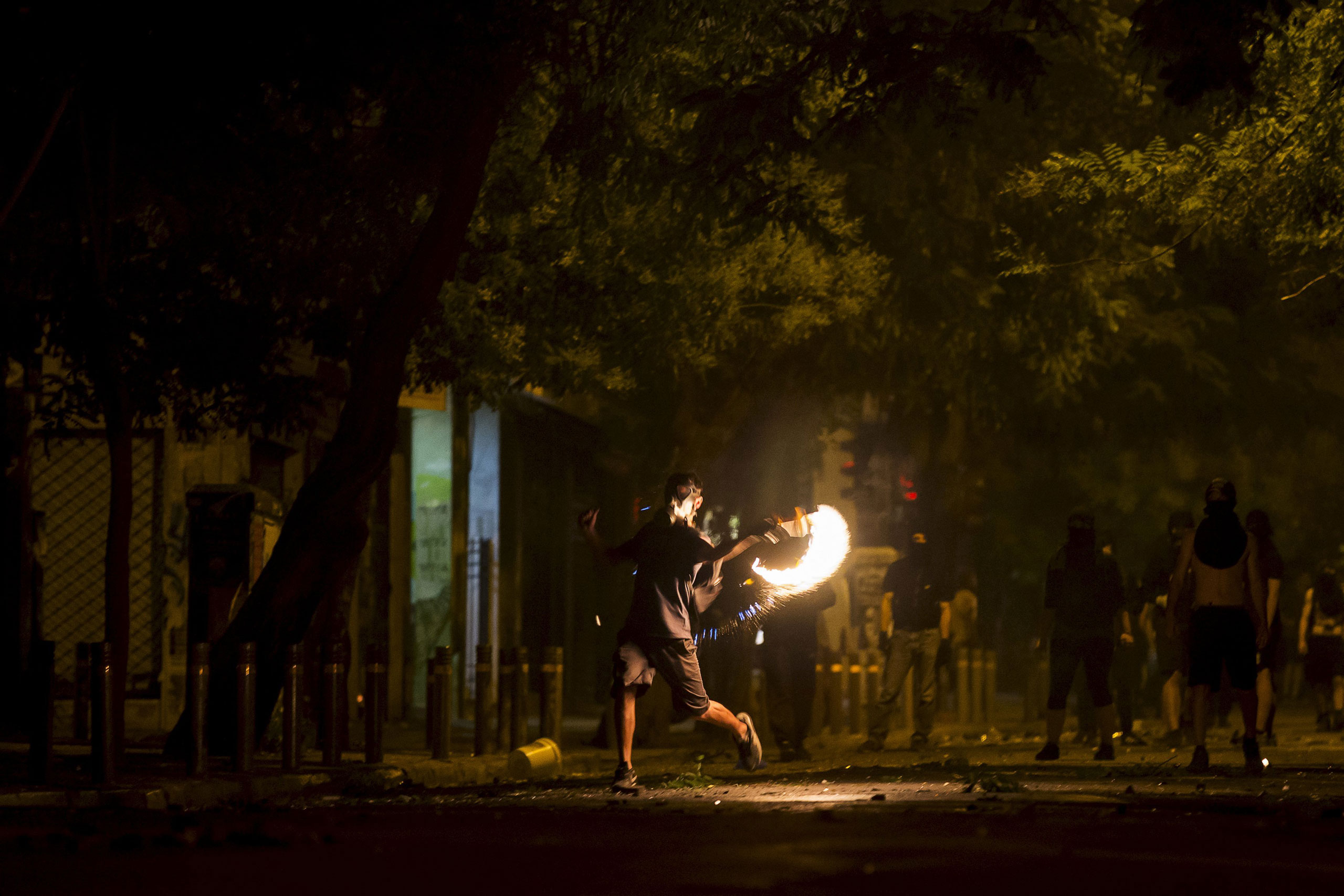 A masked youth throws a petrol bomb at riot police during minor clashes in central Athens on July 5, 2015.