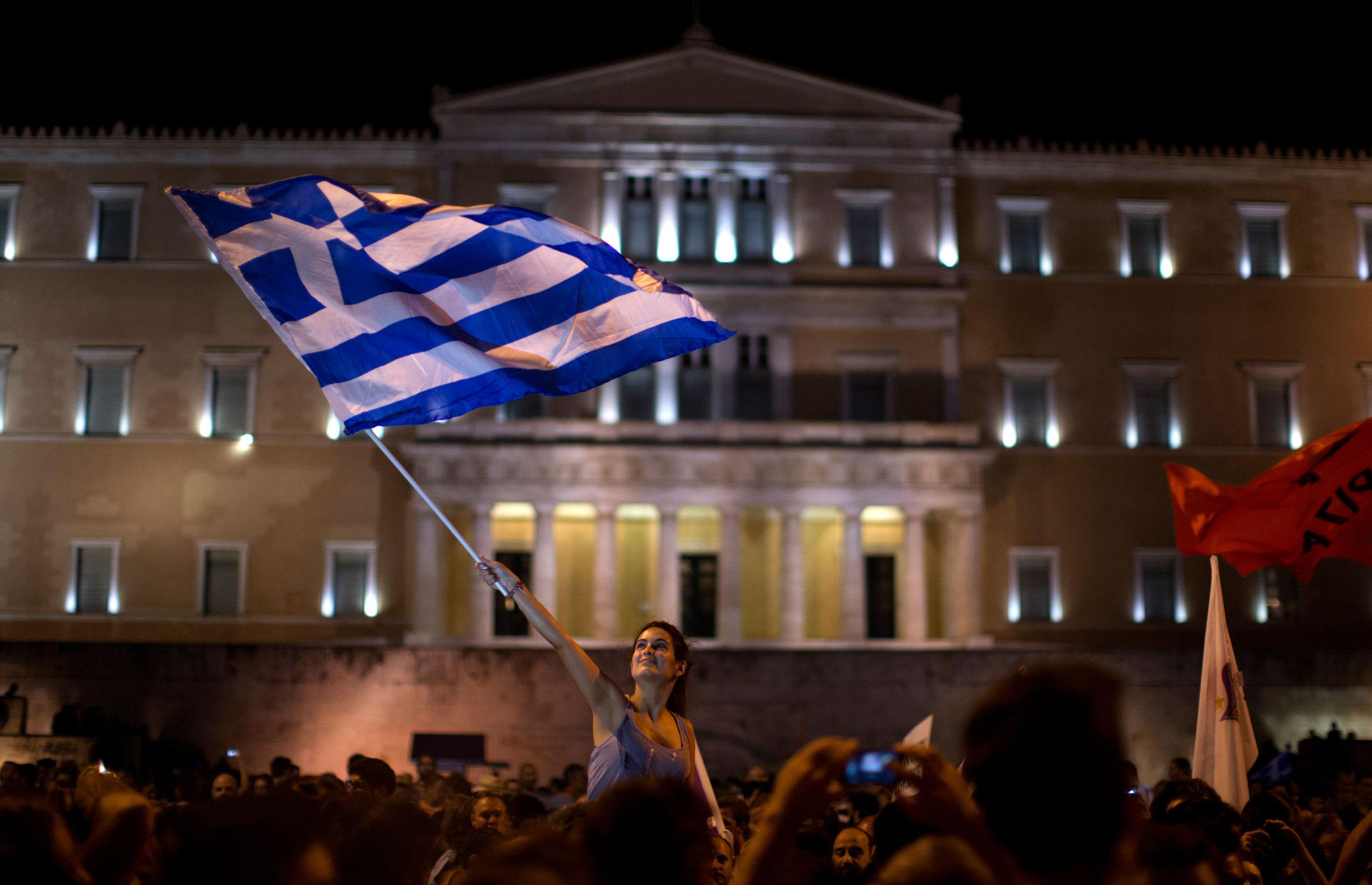 A supporter of the No vote waves a Greek flag in front of the parliament after the results of the referendum at Syntagma square in Athens,on July 5, 2015.