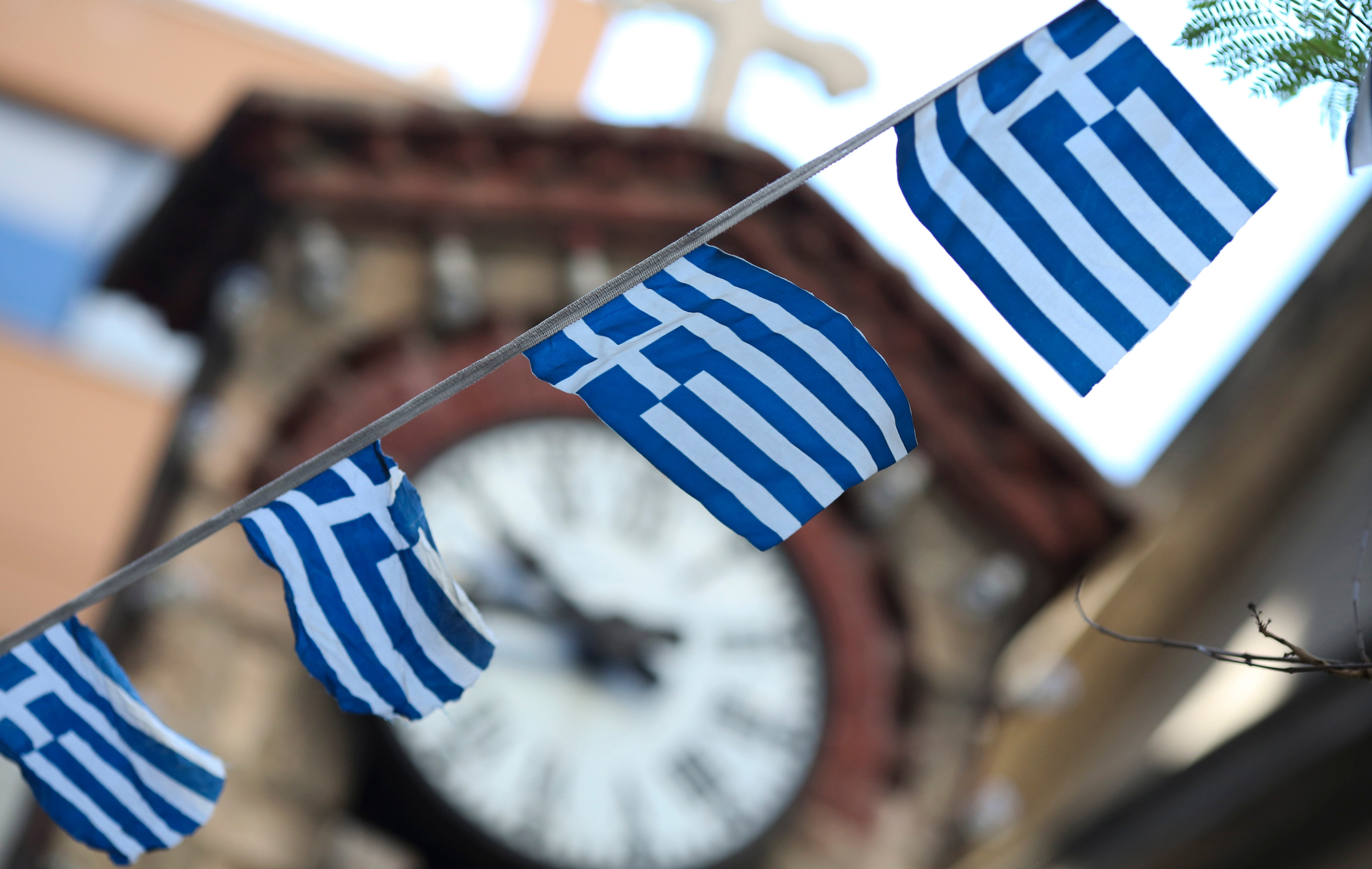 Greek national flag bunting hangs in front of a church clock tower in the Plaka district of Athens, Greece, on Thursday, July 2, 2015.