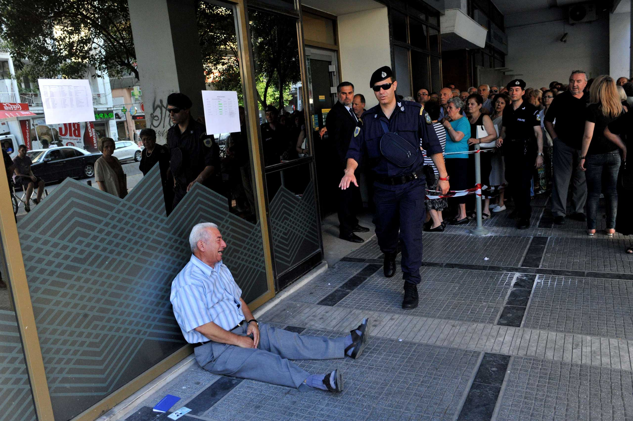Giorgos Chatzifotiadis, sitting on the ground crying outside a national bank branch, as pensioners queue to withdraw their pensions, with a limit of 120 euros, in Thessaloniki, on July 3, 2015.