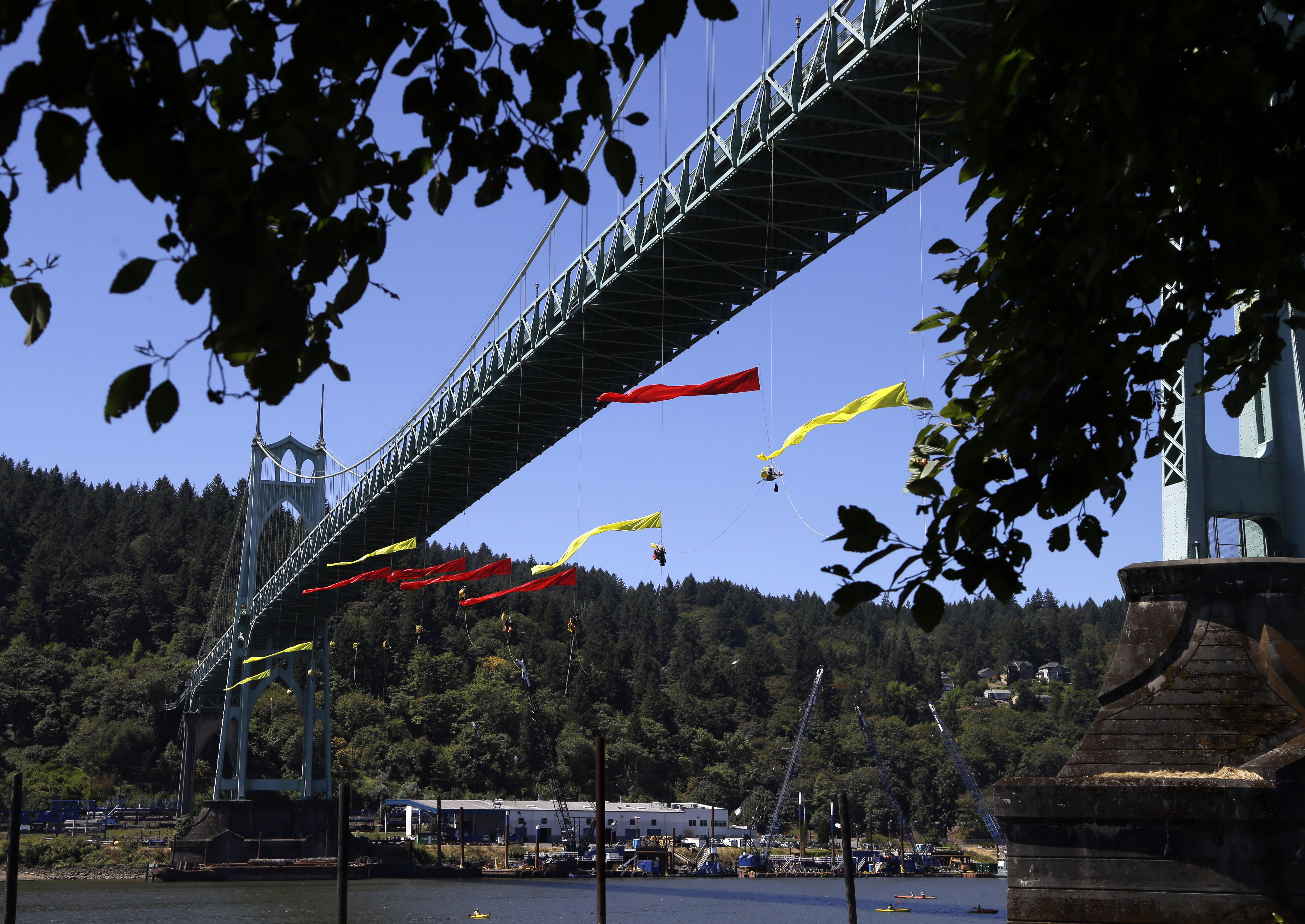 Activists unfurl colored banners while hanging from the St. Johns bridge in Portland on July 29, 2015, to protest  the departure of Royal Dutch Shell PLC icebreaker Fennica.