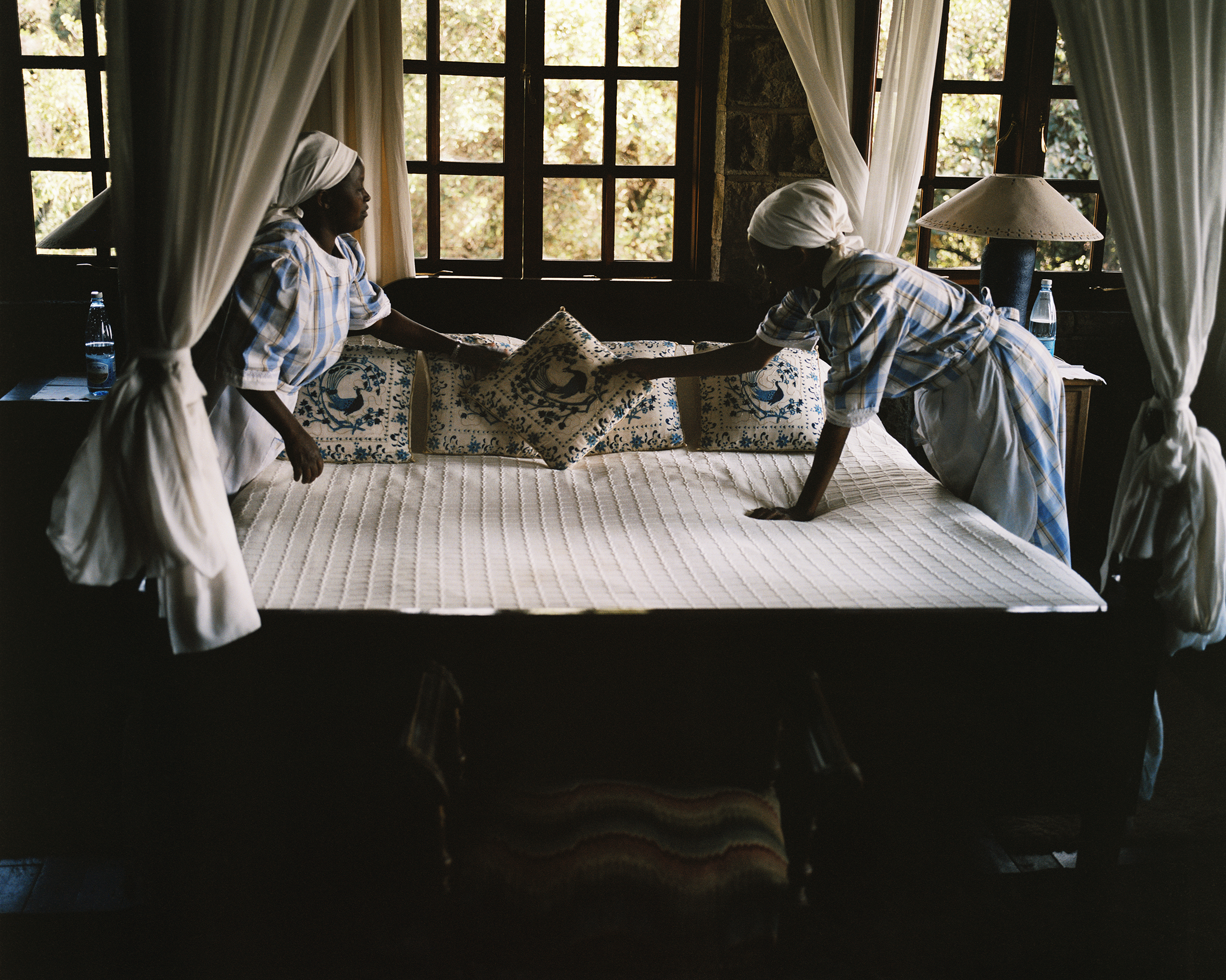 Maids prepare a room for a guest in a wealthy Kenyan household.                               2011
