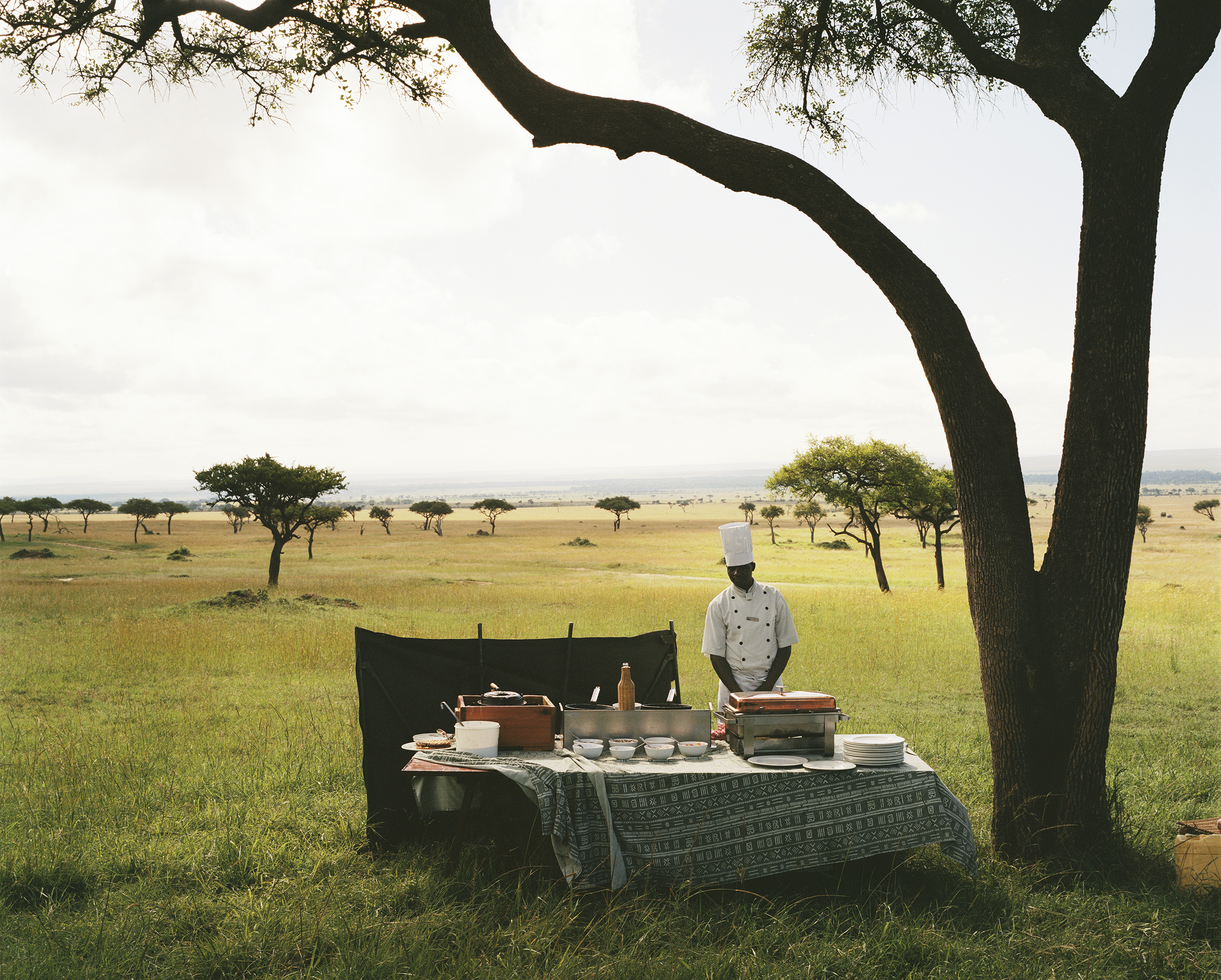 A chef from a nearby luxury lodge waits for his guests to arrive from a hot air balloon excursion before serving them champagne in the middle of the Maasai Mara National Reserve, Kenya.                               2012