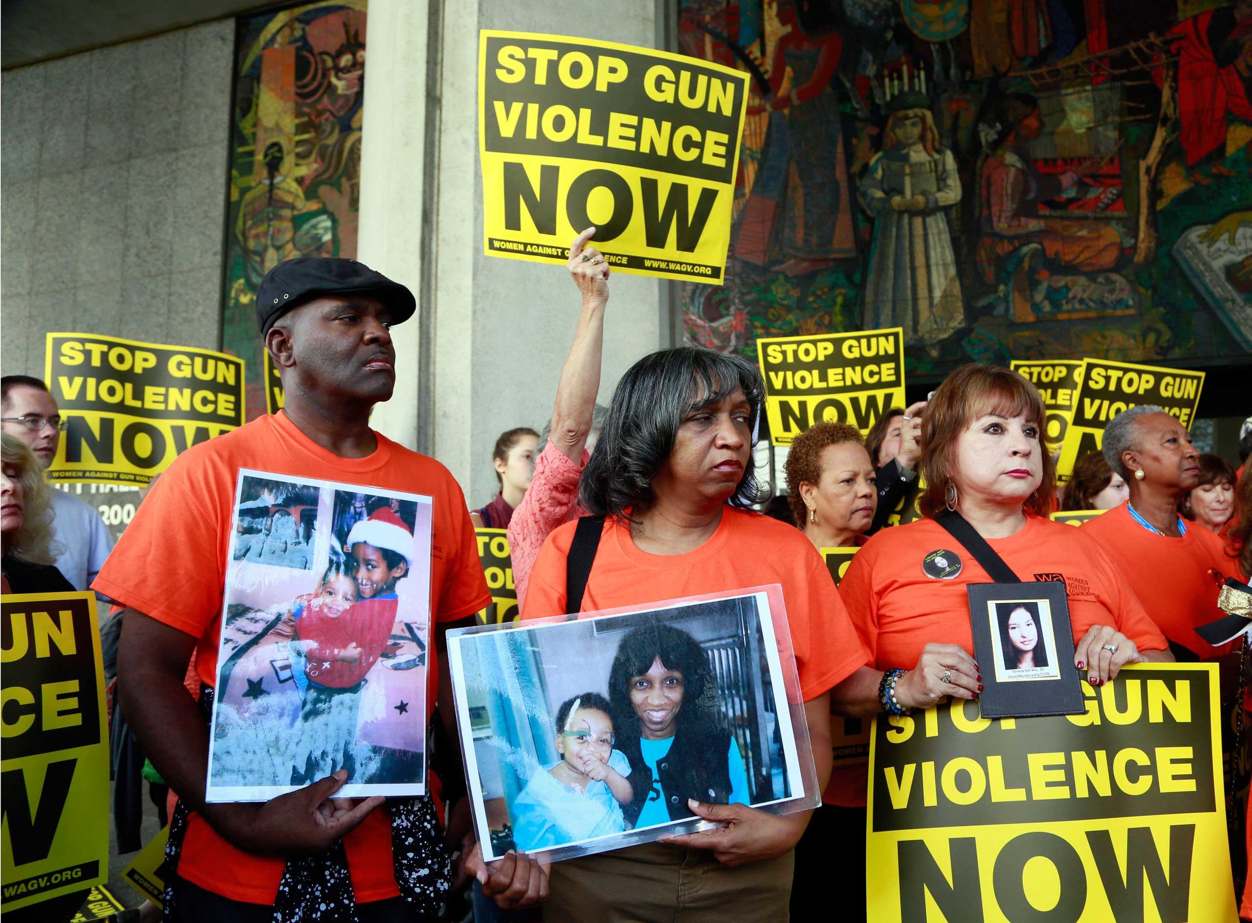Parents of victims of gun violence, pastor Ruett Foster, from left, his wife Rhonda and Anna Del Rio hold pictures of their late children, during a rally supporting a city ordinance to ban the possession of high-capacity gun magazines outside Los Angeles City Hall, on July 28, 2015.