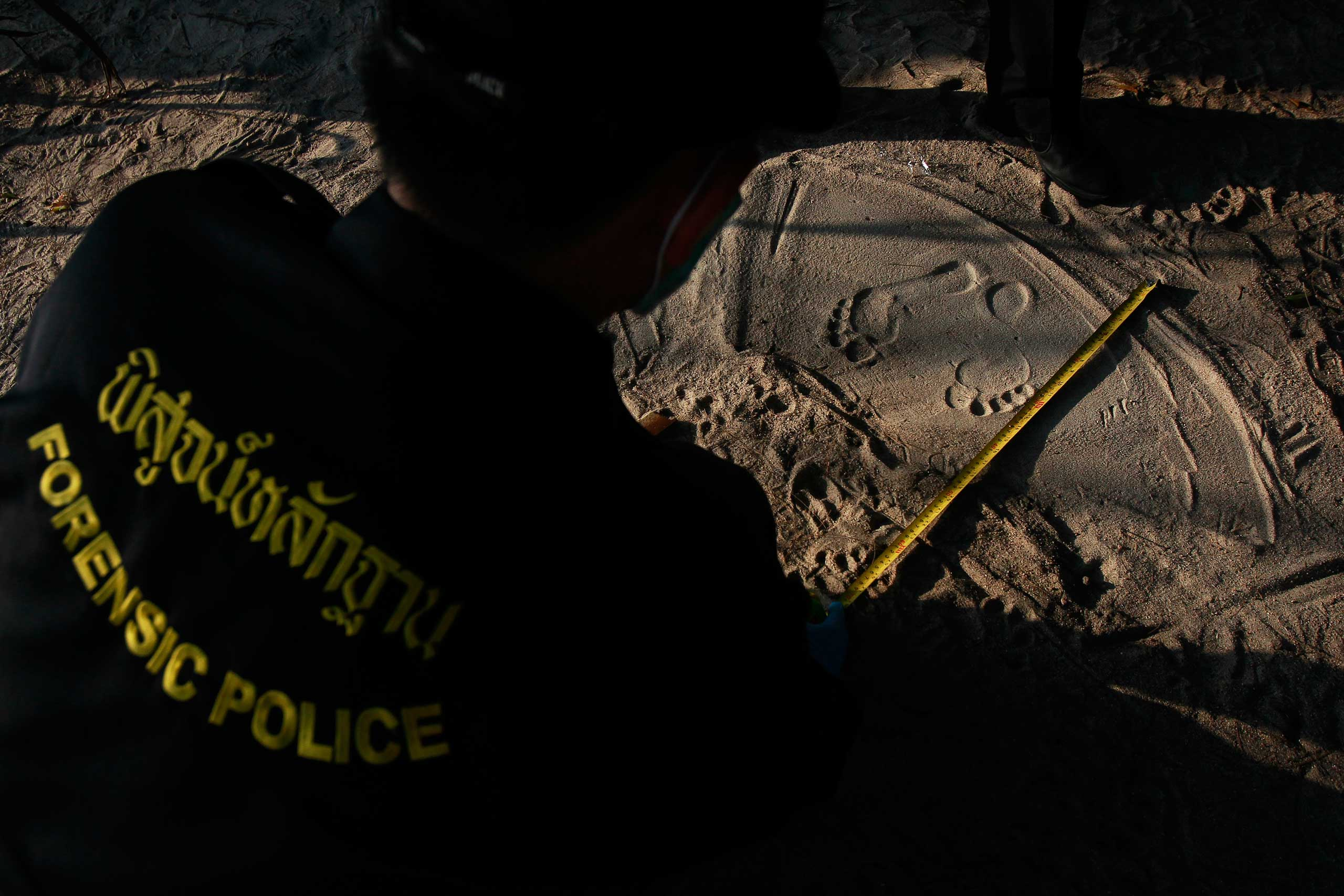 Police measure footprints of a man as data is collected from people who work near the spot where bodies of two killed British tourists were found, on the island of Koh Tao, Thailand, on Sept. 19, 2014