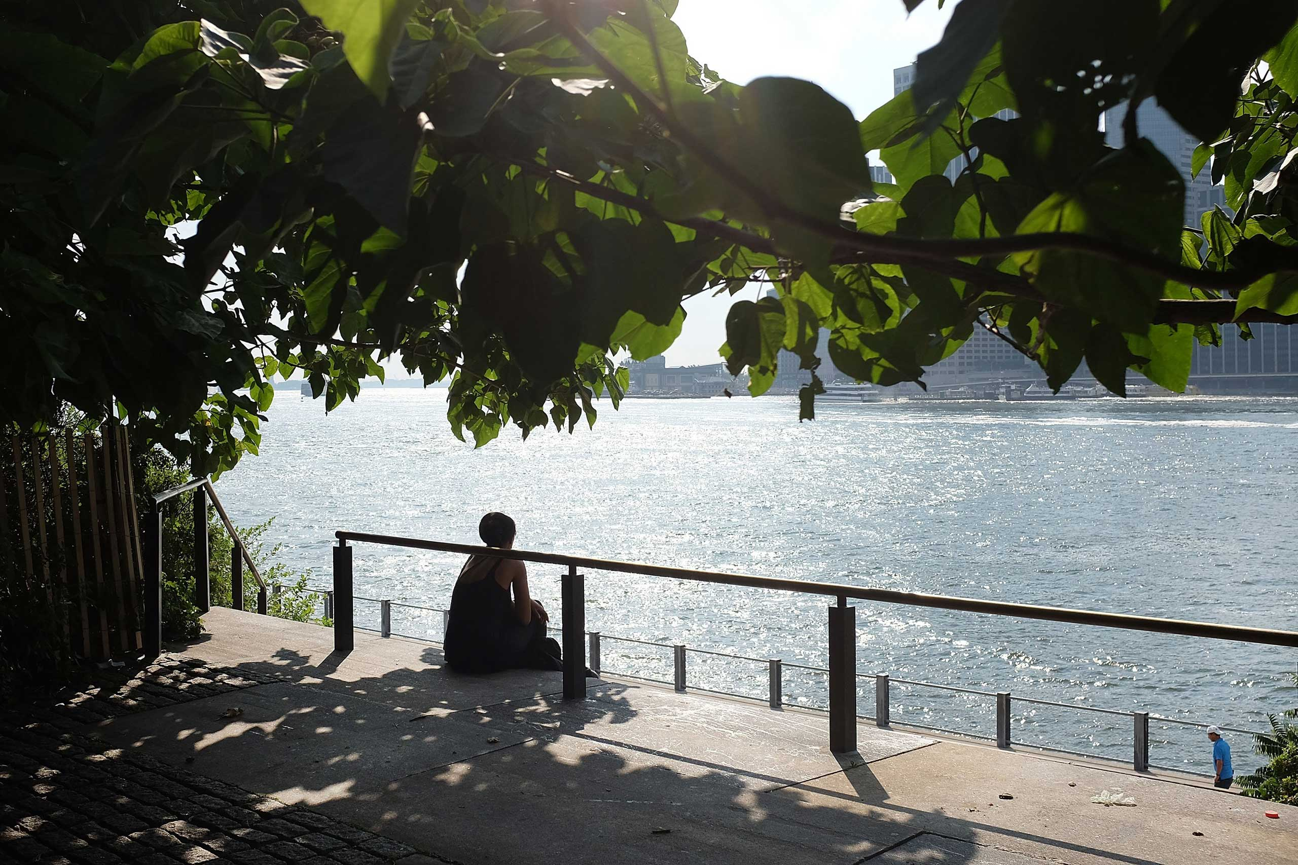A woman relaxes by the East River on a sweltering hot afternoon in New York, on July 28, 2015.