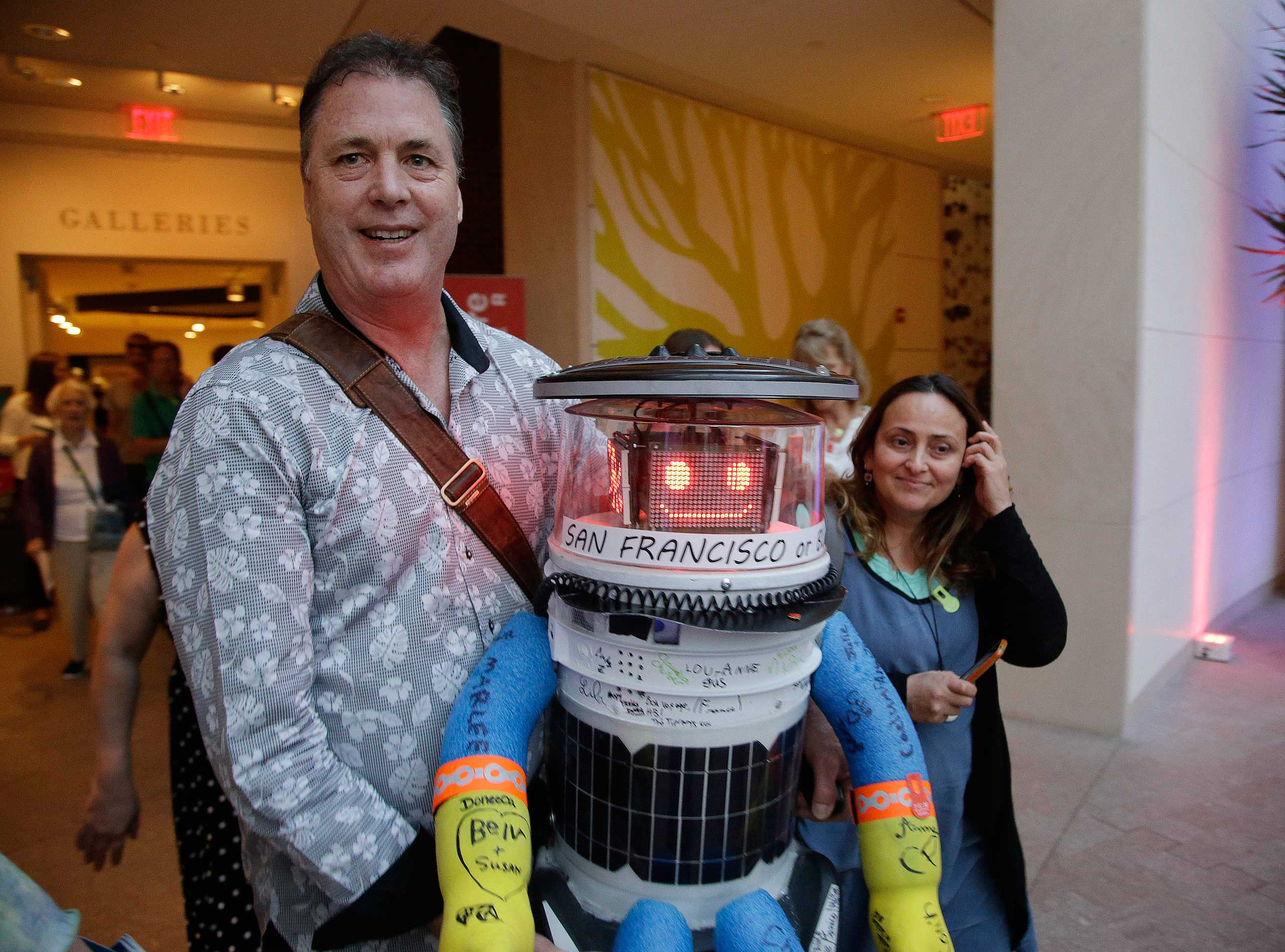 Co-creator David Harris Smith carries hitchBOT, a hitchhiking robot, during its' introduction to an American audience at the Peabody Essex Museum in Salem, Mass. on July 16, 2015.
