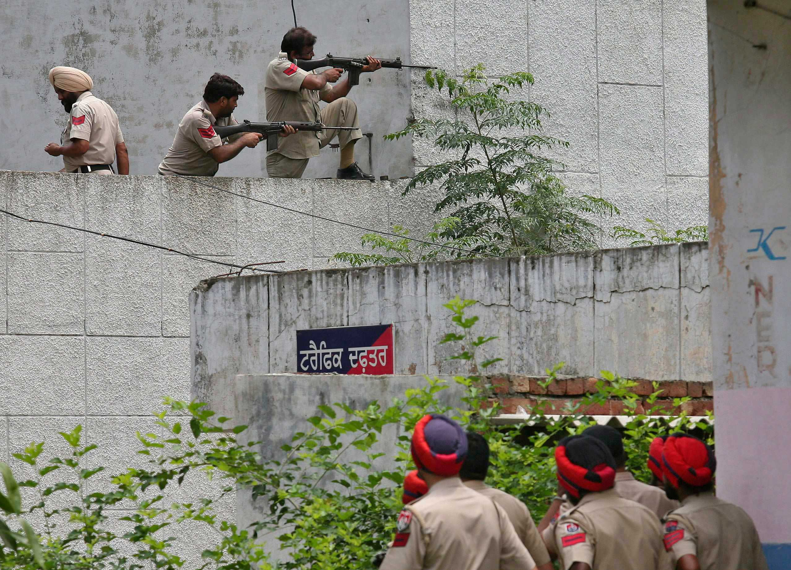 Indian policemen take their positions as their colleagues watch next to a police station during a gunfight at Dinanagar town in Gurdaspur district of Punjab, India on July 27, 2015.