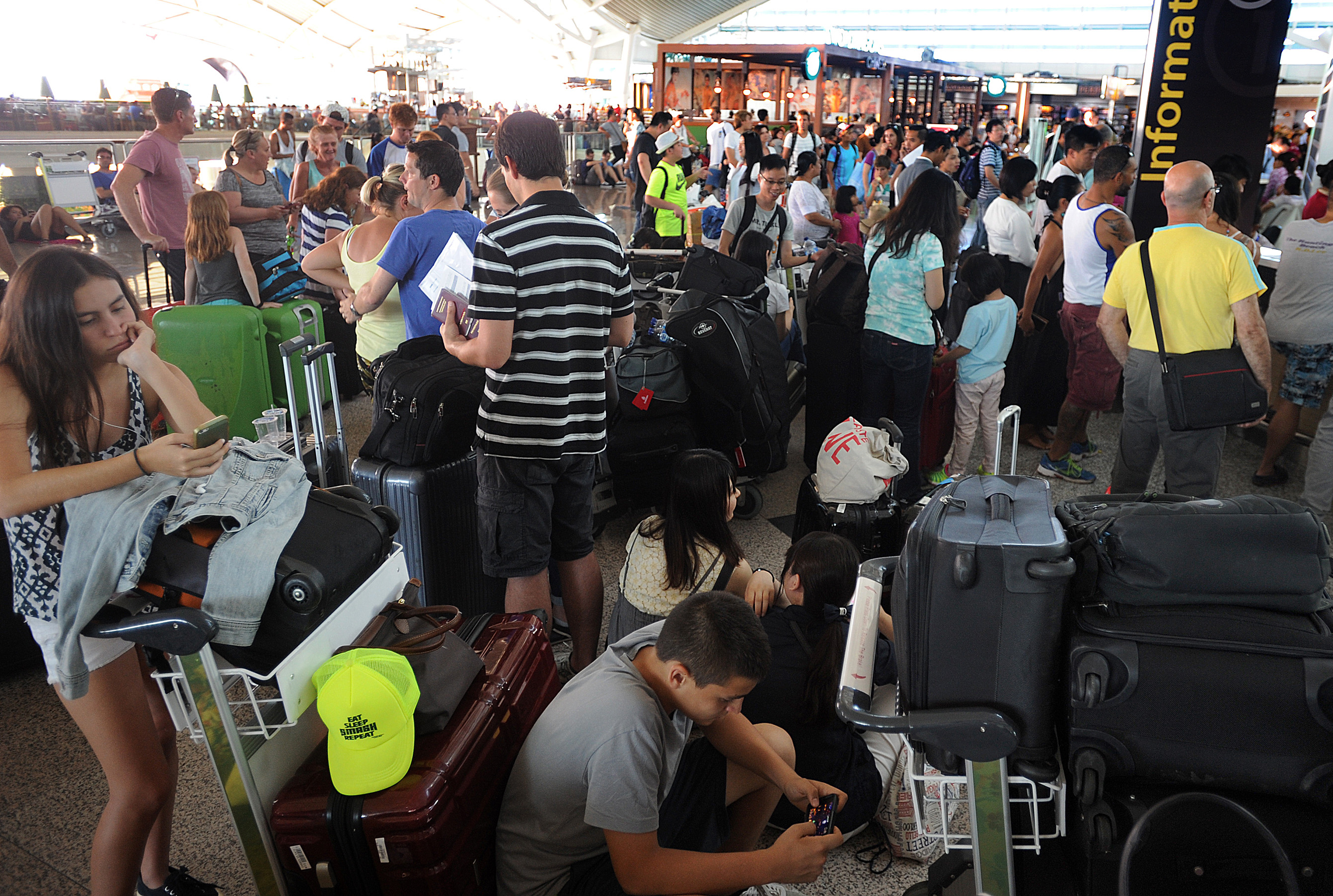 Travelers wait as flights are canceled at Ngurah Rai International Airport in Bali, Indonesia, on July 12, 2015, because of the eruption of Mount Raung in East Java province