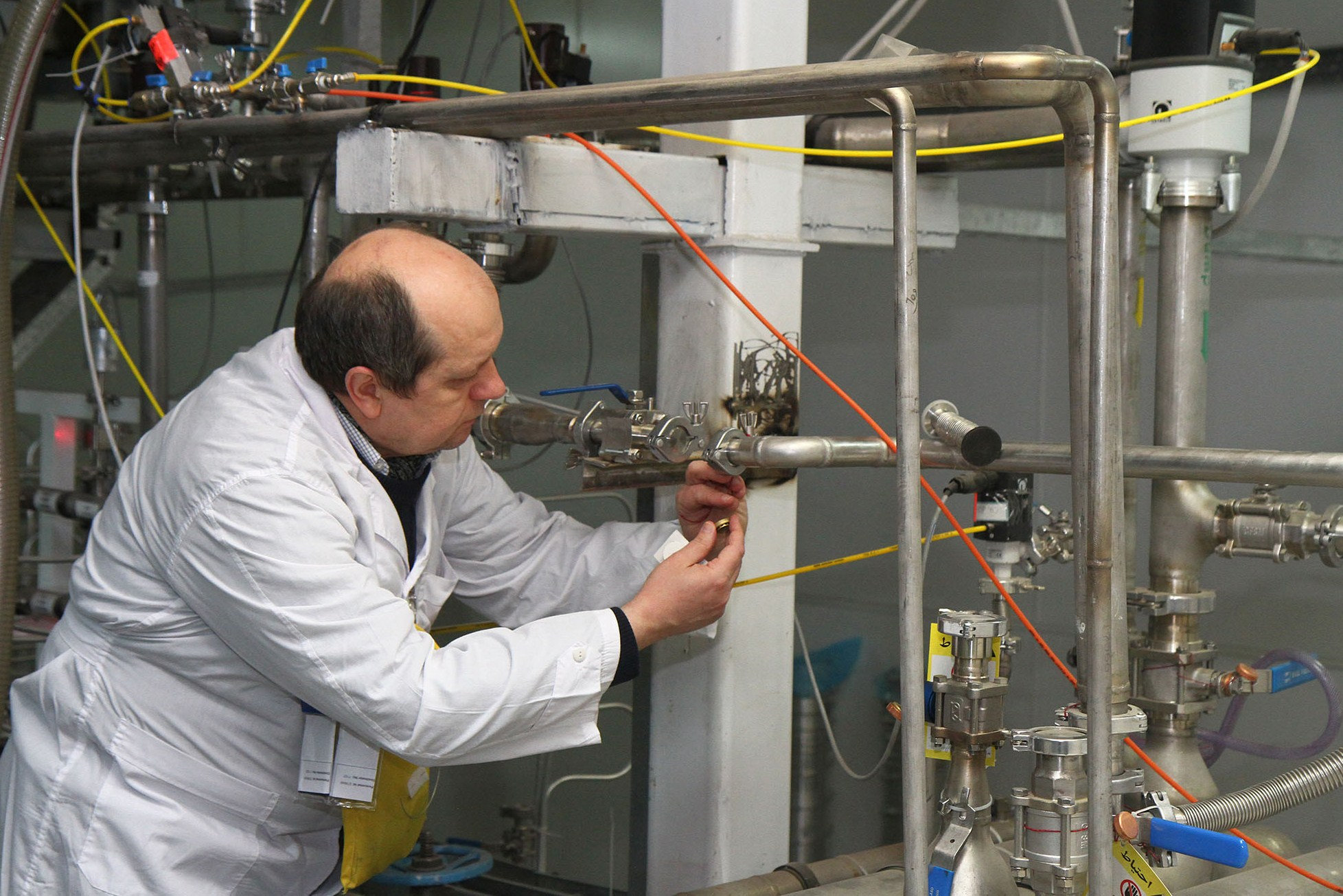 An International Atomic Energy Agency (IAEA) inspector disconnects the connections between the twin cascades for 20 percent uranium production at nuclear power plant of Natanz, some 300 kilometres south of Tehran on Jan. 20, 2014.