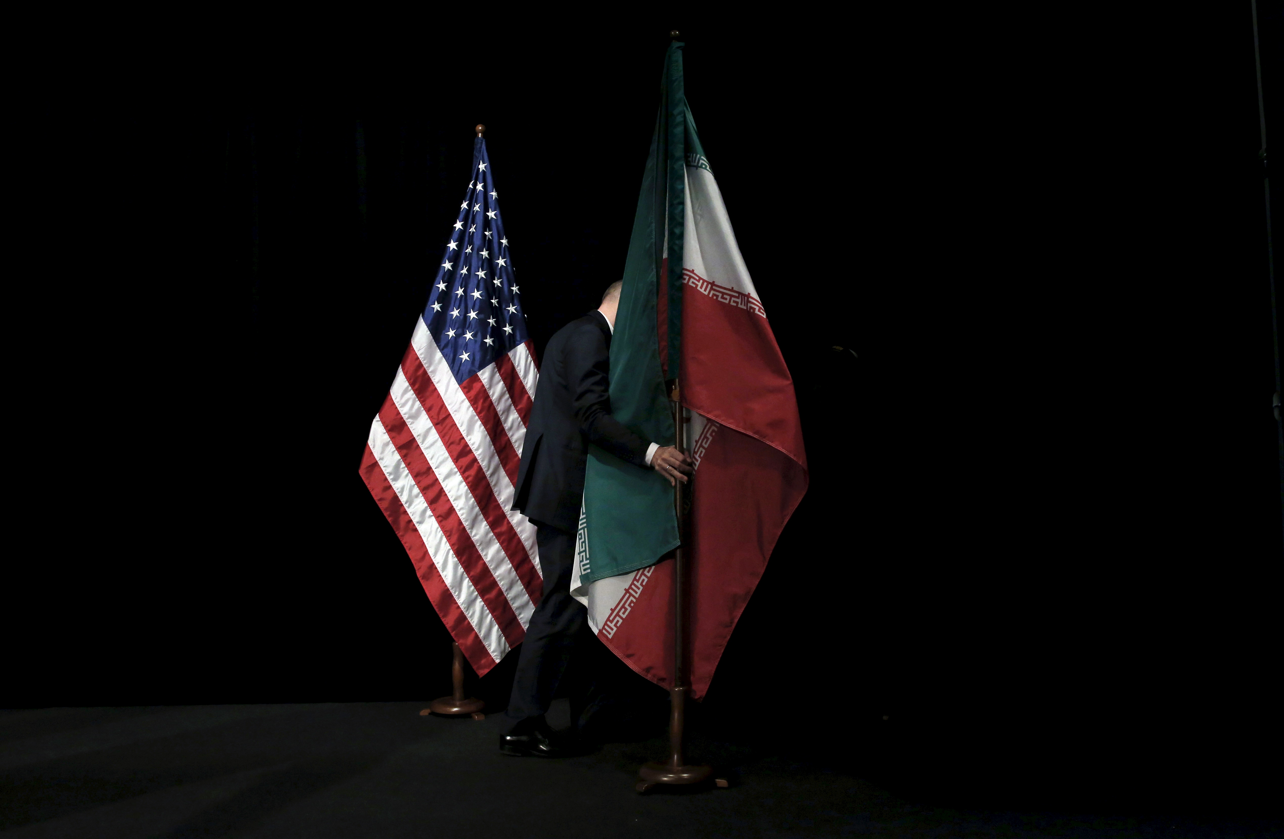 A staff member removes the Iranian flag from the stage after a group picture with foreign ministers and representatives of Unites States, Iran, China, Russia, Britain, Germany, France and the European Union during the Iran nuclear talks at the Vienna International Center in Vienna on July 14, 2015.