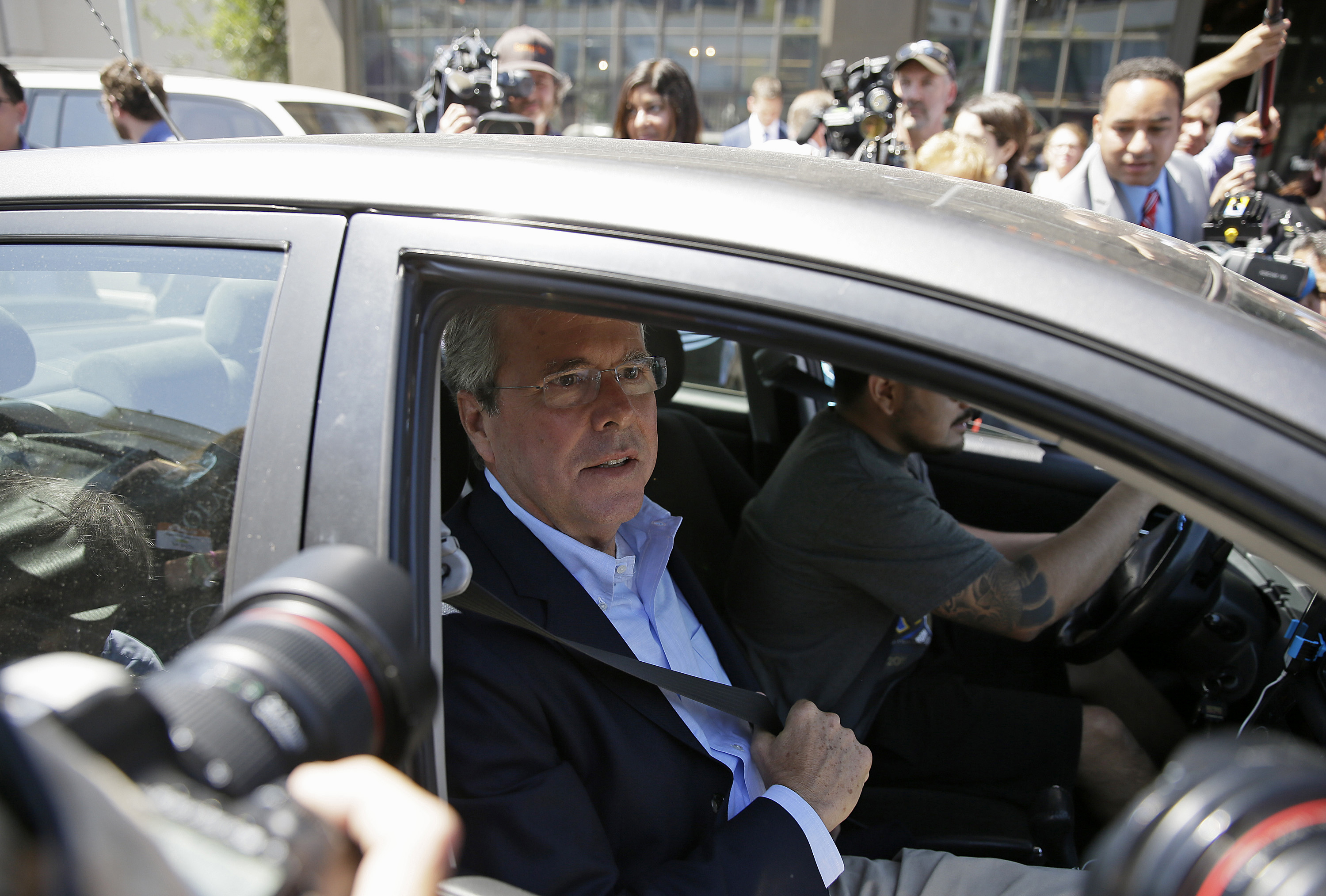 Republican presidential candidate, former Florida Gov. Jeb Bush, puts on his seat belt getting into an Uber car after speaking at Thumbtack, an online startup in San Francisco.