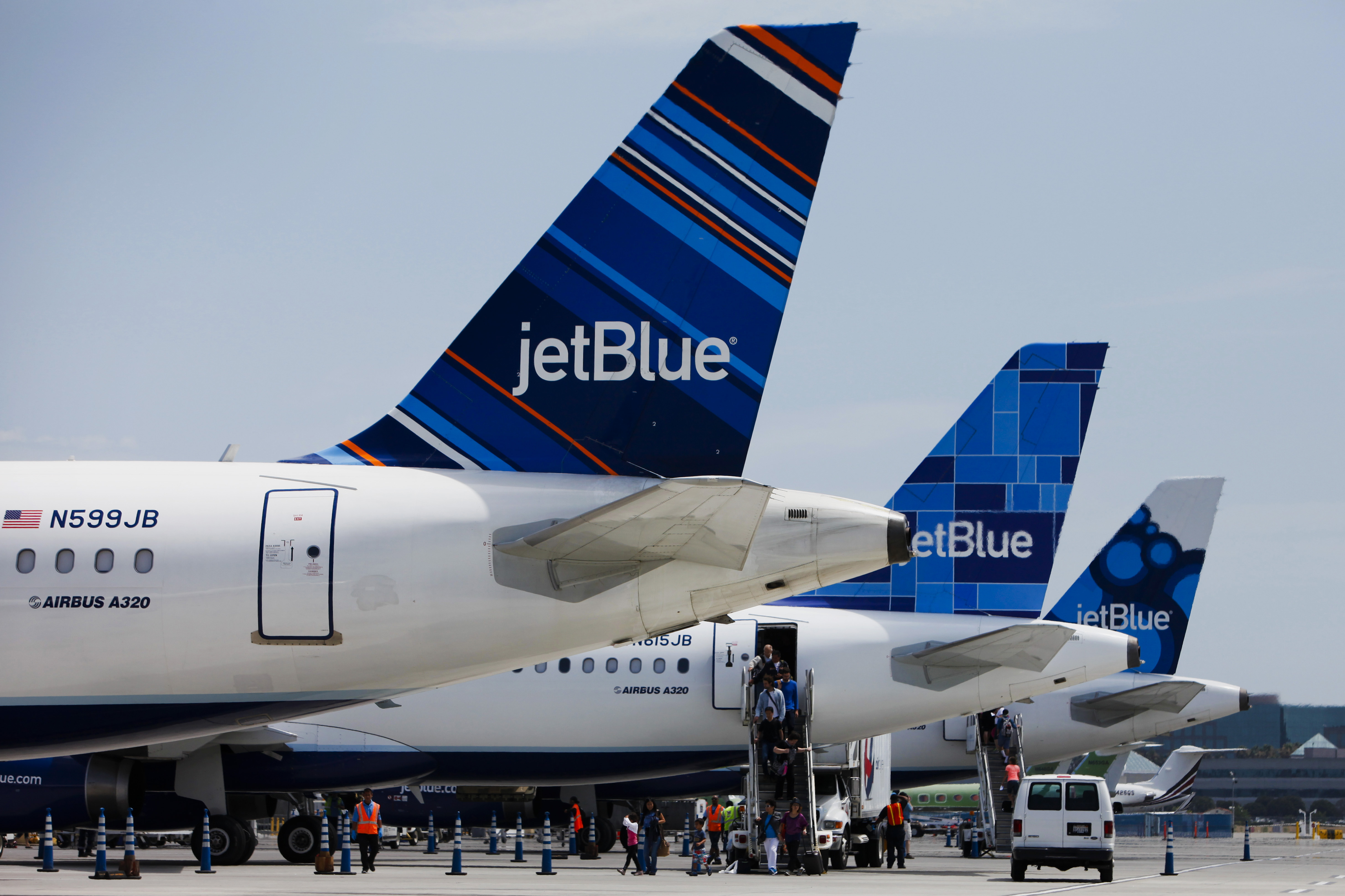 Passengers exit a JetBlue Airways Corp. plane at Long Beach Airport in Long Beach, Calif., on July 22, 2013.