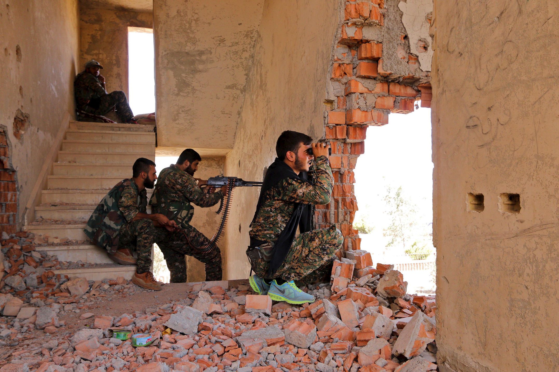 Kurdish People's Protection Units (YPG) fighters take up positions inside a damaged building in al-Vilat al-Homor neighborhood in Hasaka city, as they monitor the movements of Islamic State fighters who are stationed in Ghwayran neighborhood in Hasaka city, Syria on July 22, 2015.