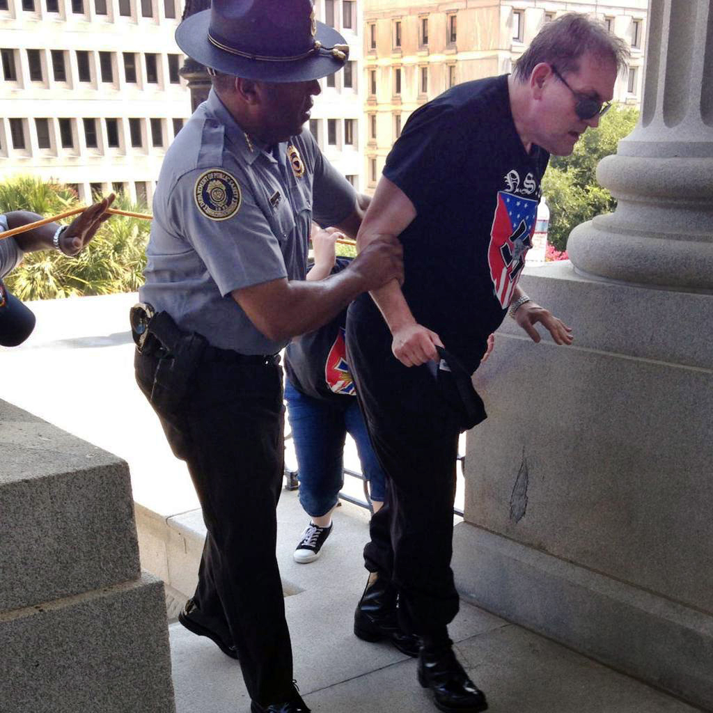 Police officer Leroy Smith helps a man wearing National Socialist Movement attire up the stairs during a rally on July 18, 2015, in Columbia, S.C.