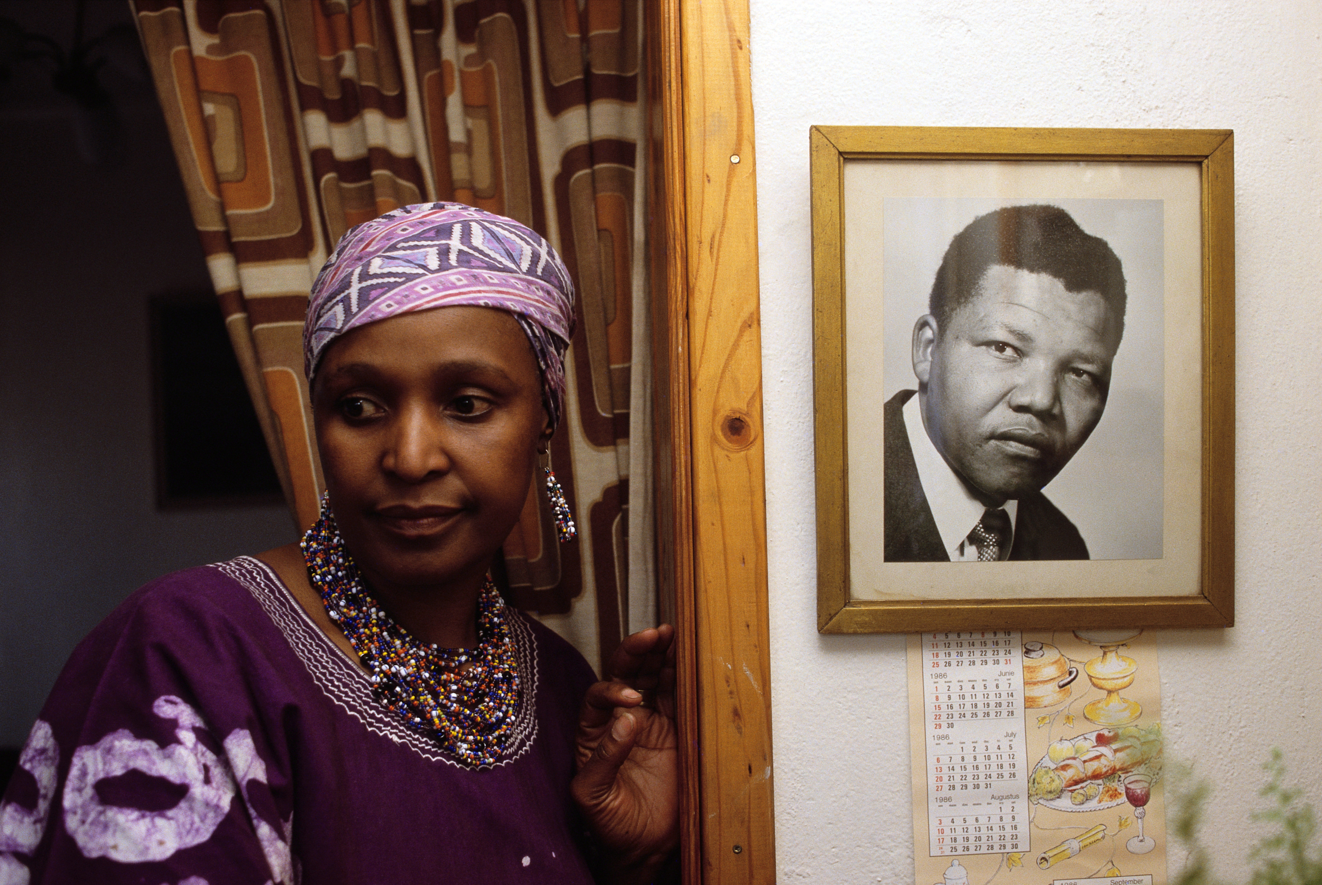 Winnie Mandela stands by a portrait of her then husband in their Soweto home, 1985.
