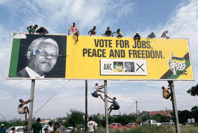 Mandela supporters perch on a billboard in Durban, April 1994.