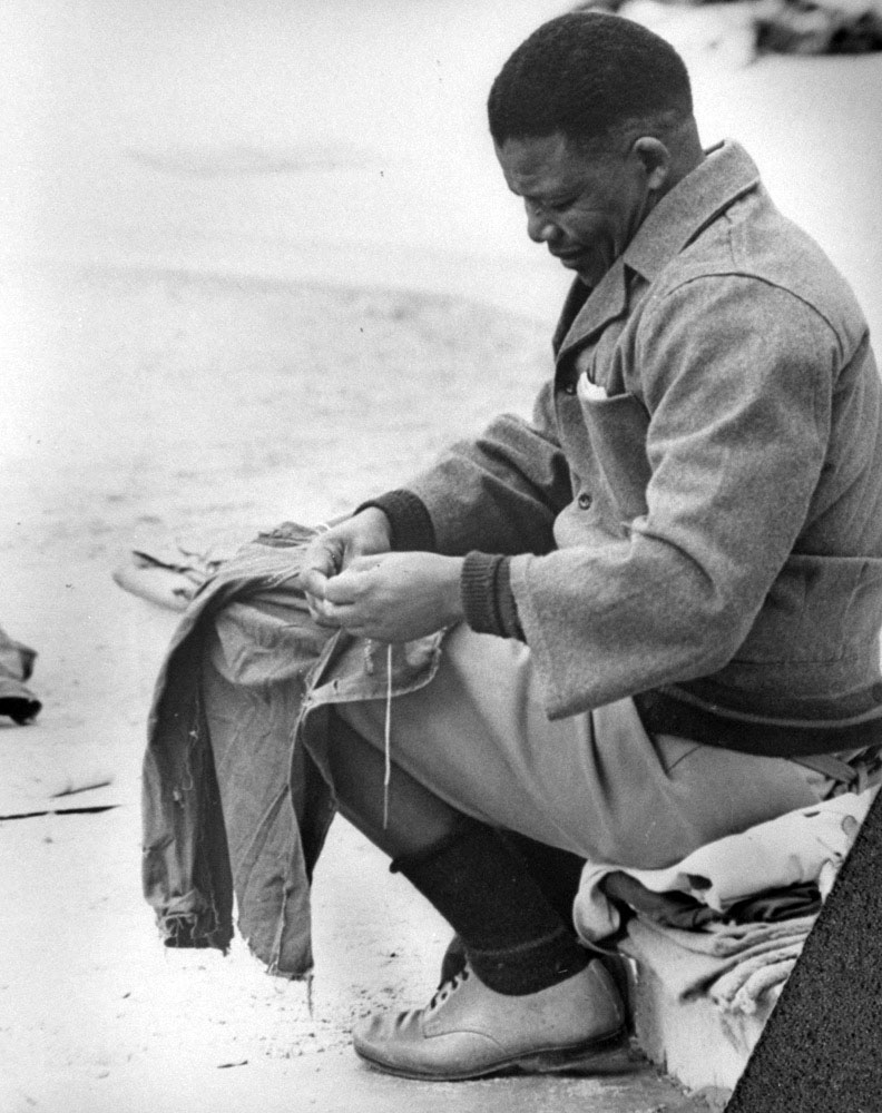 Mandela sews prison clothes by the shore in 1964. He was sent to the infamous jail at Robben Island, a barren rock off the coast near Cape Town, in 1963 in part for his activities supporting the ANC's militant wing, Umkhonto we Sizwe (the Spear of the Nation). His 27-year-long imprisonment made him the world's most famous political prisoner.