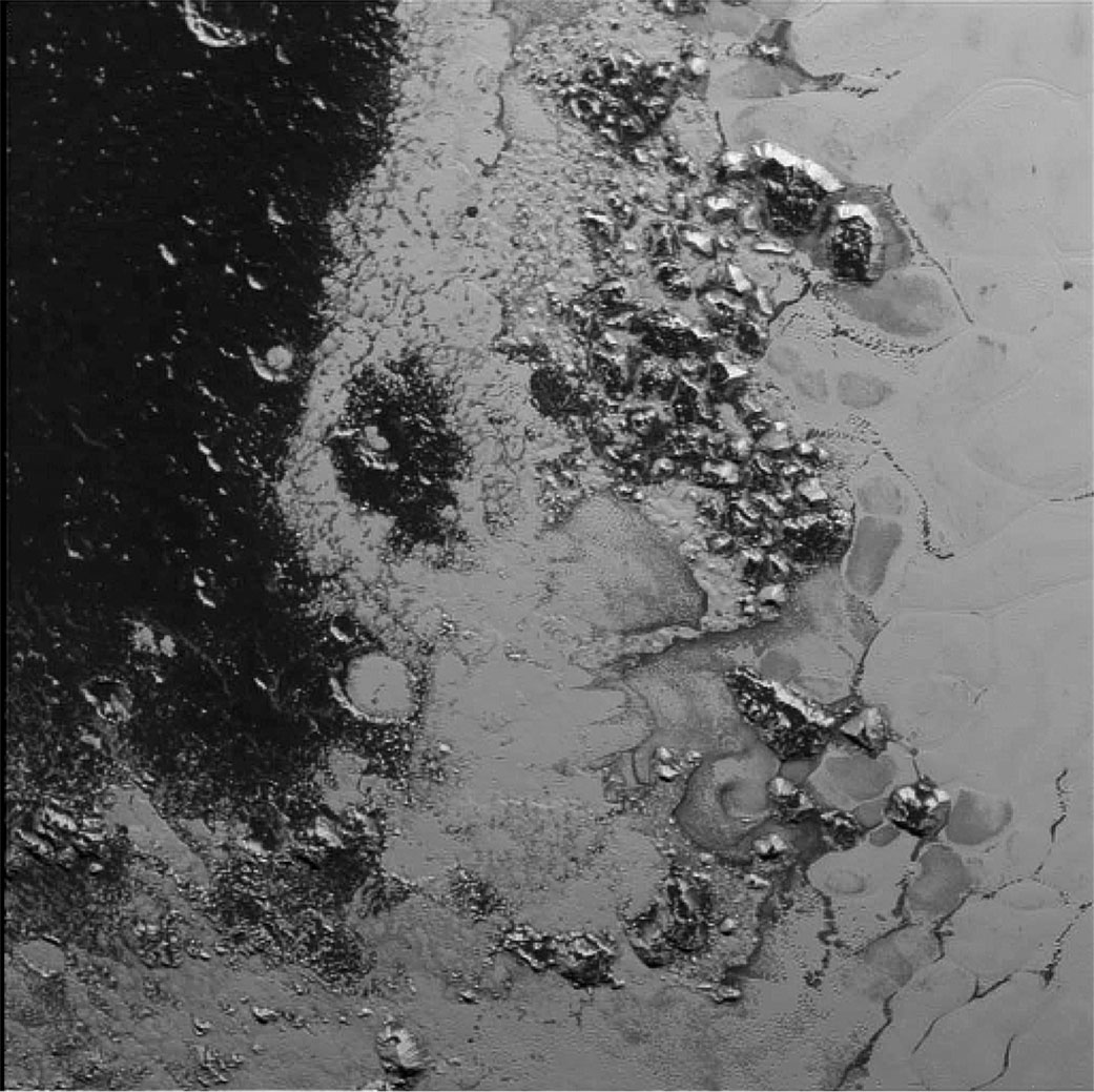 A newly discovered mountain range lies near the southwestern margin of Pluto's heart-shaped Tombaugh Regio (Tombaugh Region), situated between bright, icy plains and dark, heavily-cratered terrain.