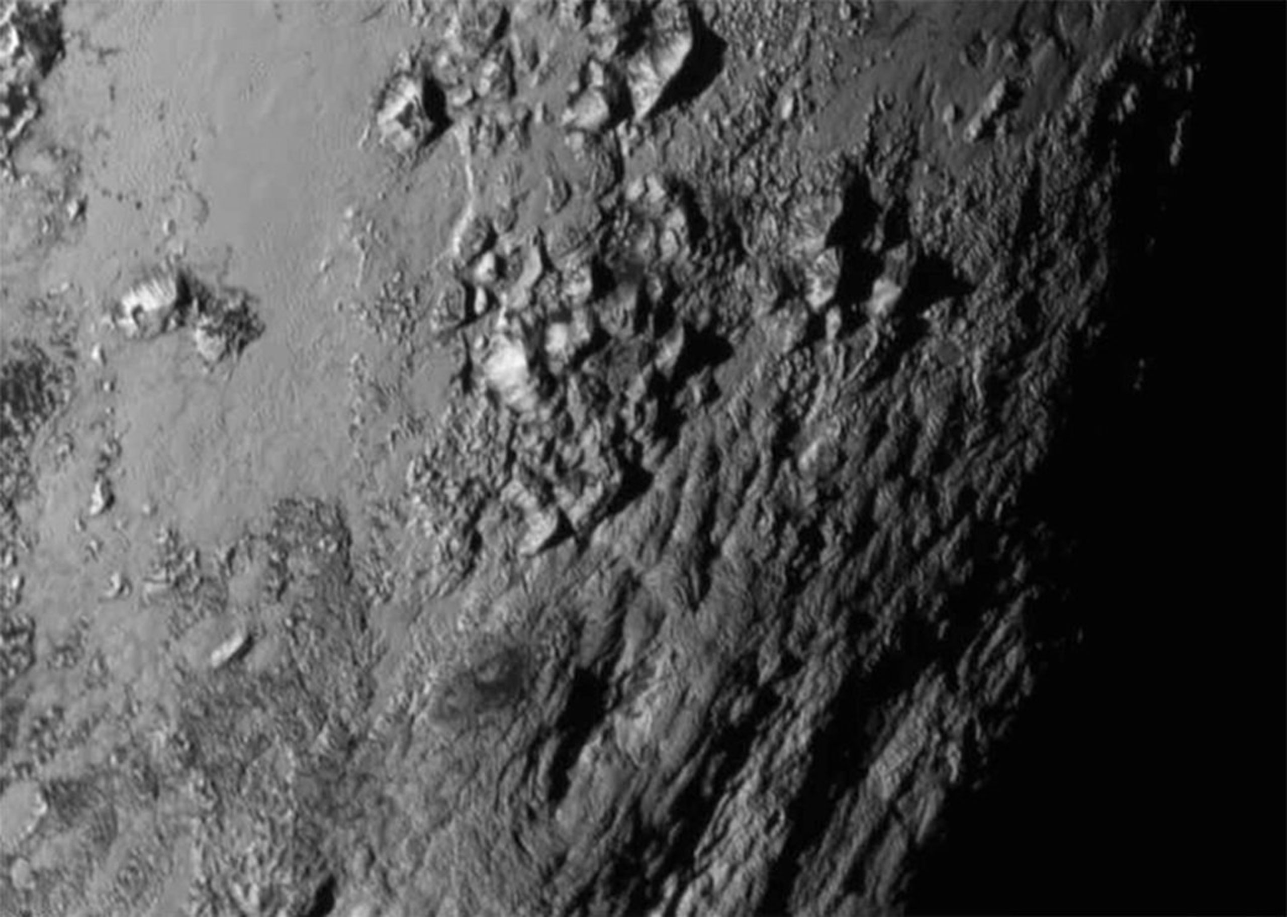 A close-up image of a region near  Pluto's equator shows a range of mountains rising as high as 11,000 feet (3,500 meters) taken by NASA's New Horizons spacecraft as it passed within 7,800 feet of the dwarf planet on July 14, 2015.
